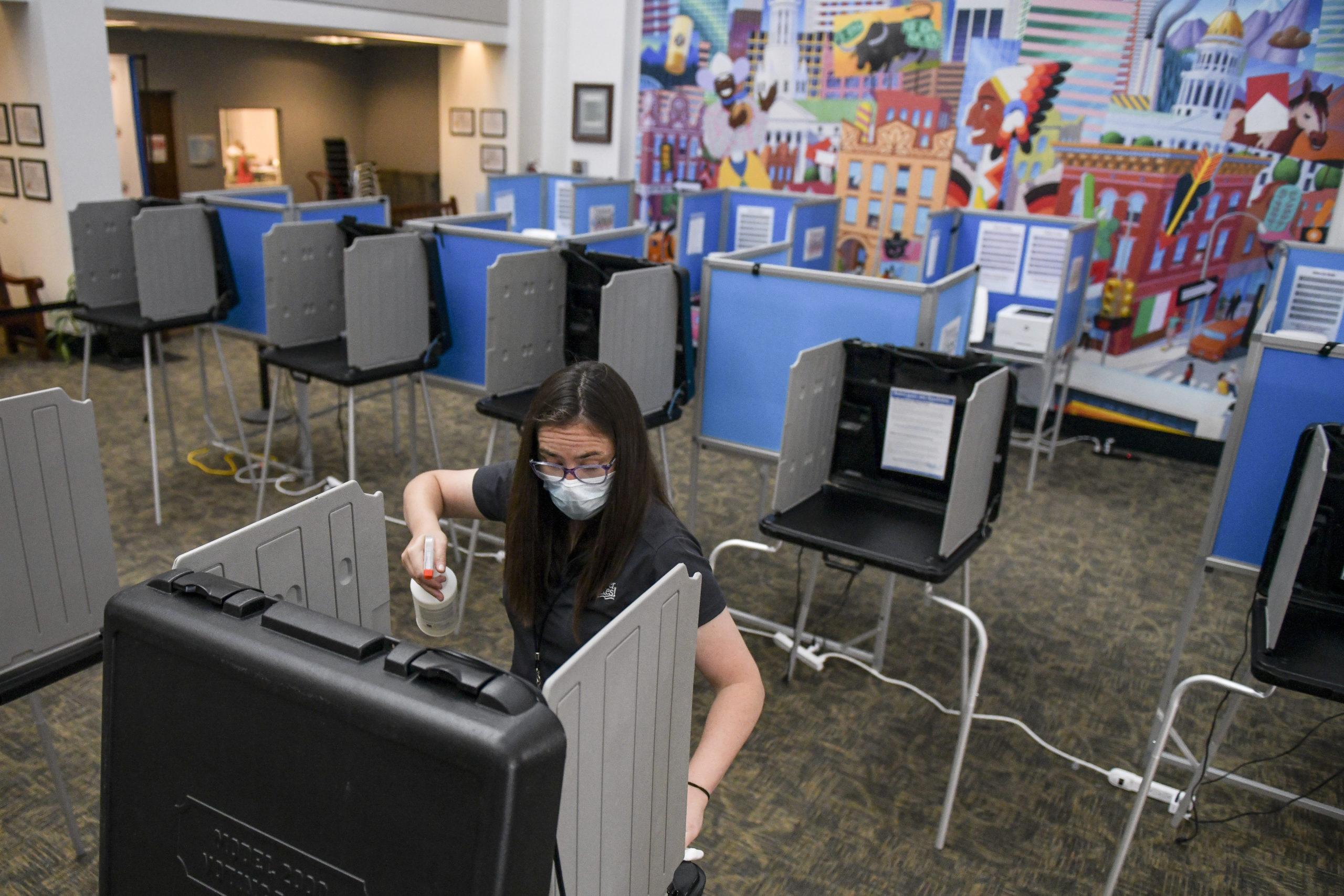 DENVER, CO - JUNE 30: Election judge Miriam Dubinsky sanitizes a voting booth as people vote in the primary election on June 30, 2020 in Denver, Colorado. Voters will decide between former Gov. John Hickenlooper and former Colorado House of Representatives Speaker Andrew Romanoff to face off in the November U.S. Senate race against Sen. Cory Gardner. (Photo by Michael Ciaglo/Getty Images)