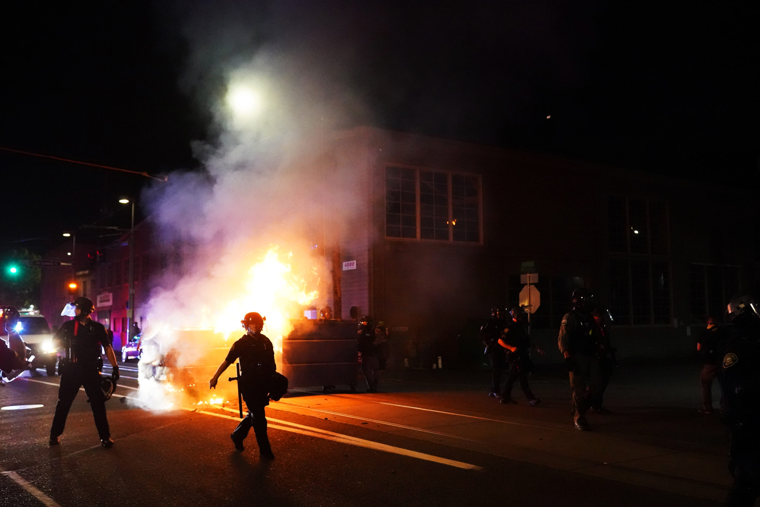 PORTLAND, OR - AUGUST 21: Portland police officers push protesters past a dumpster fire during a dispersal from in front of the Immigration and Customs Enforcement (ICE) detention facility early in the morning on August 21, 2020 in Portland, Oregon. For the second night in a row city police and federal officers clashed with protesters in South Waterfront. (Photo by Nathan Howard/Getty Images)
