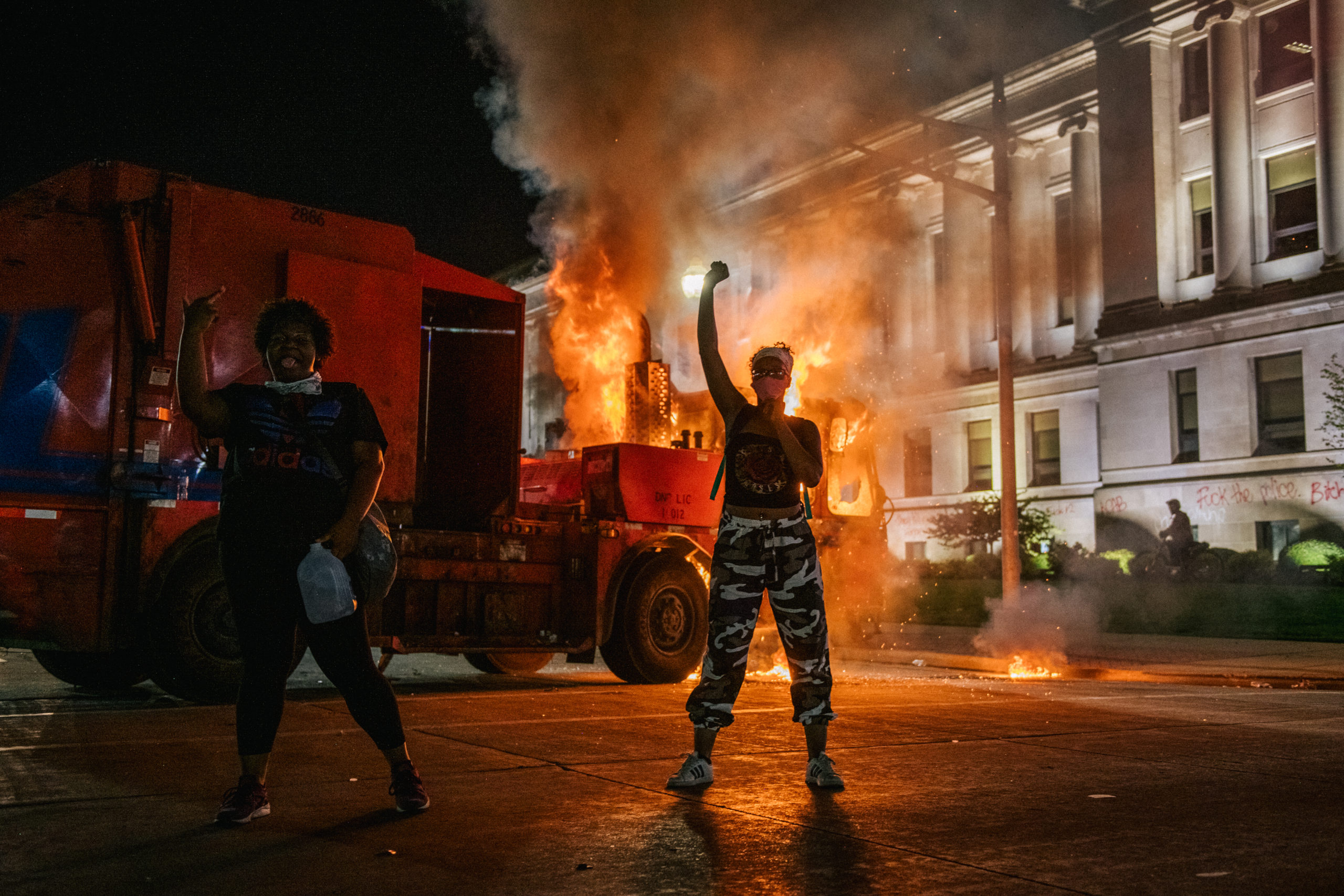 KENOSHA, WI - AUGUST 24: Demonstrators chant in front of a burning truck on August 24, 2020 in Kenosha, Wisconsin. This is the second night of rioting after the shooting of Jacob Blake, 29, on August 23. Blake was shot multiple times in the back by Wisconsin police officers after attempting to enter into the drivers side of a vehicle. (Photo by Brandon Bell/Getty Images)