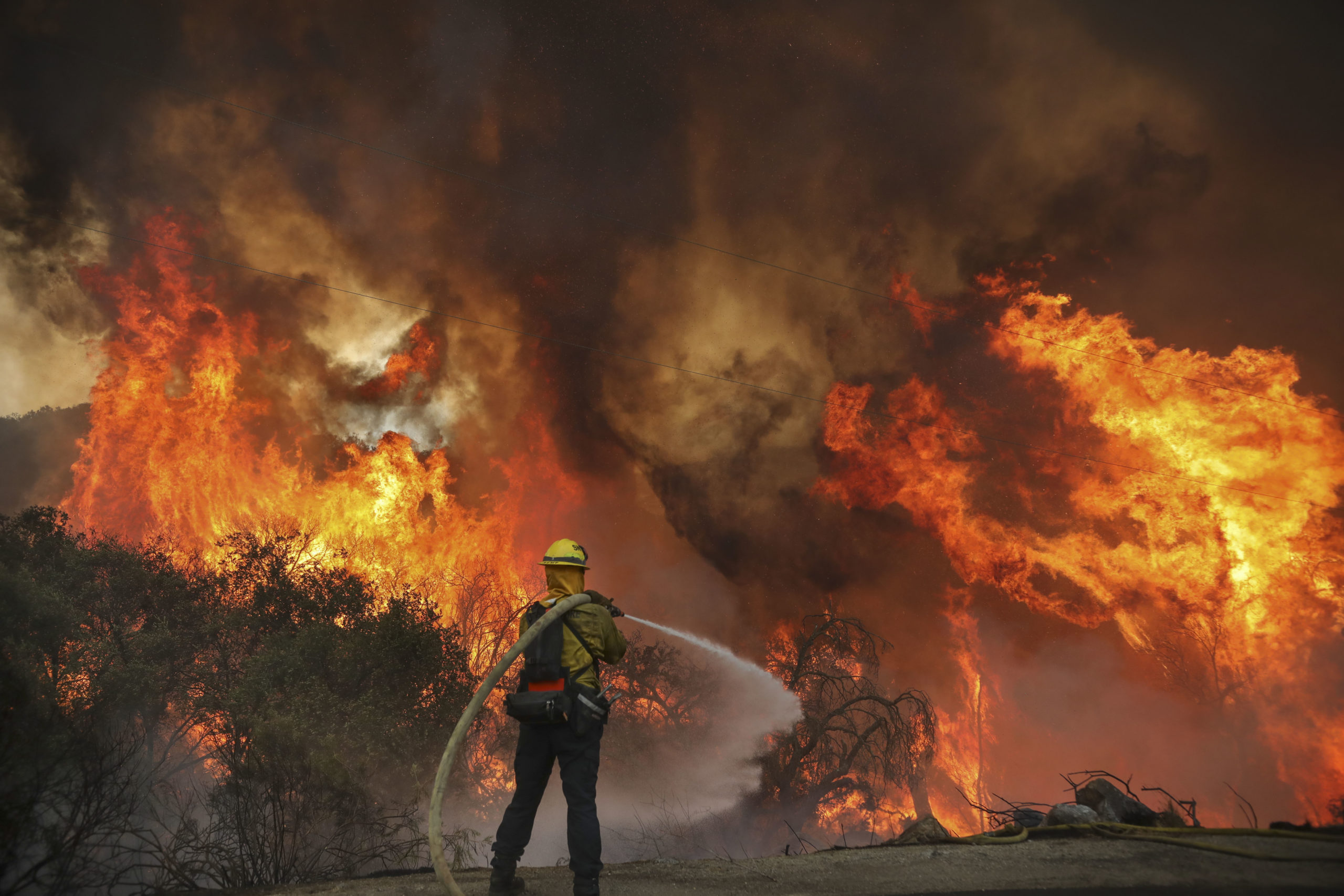 San Miguel County Firefighters battle a brush fire along Japatul Road during the Valley Fire in Jamul, California on September 6, 2020 - The Valley Fire in the Japatul Valley burned 4,000 acres overnight with no containment and 10 structures destroyed, Cal Fire San Diego said. (Photo by SANDY HUFFAKER/AFP via Getty Images)