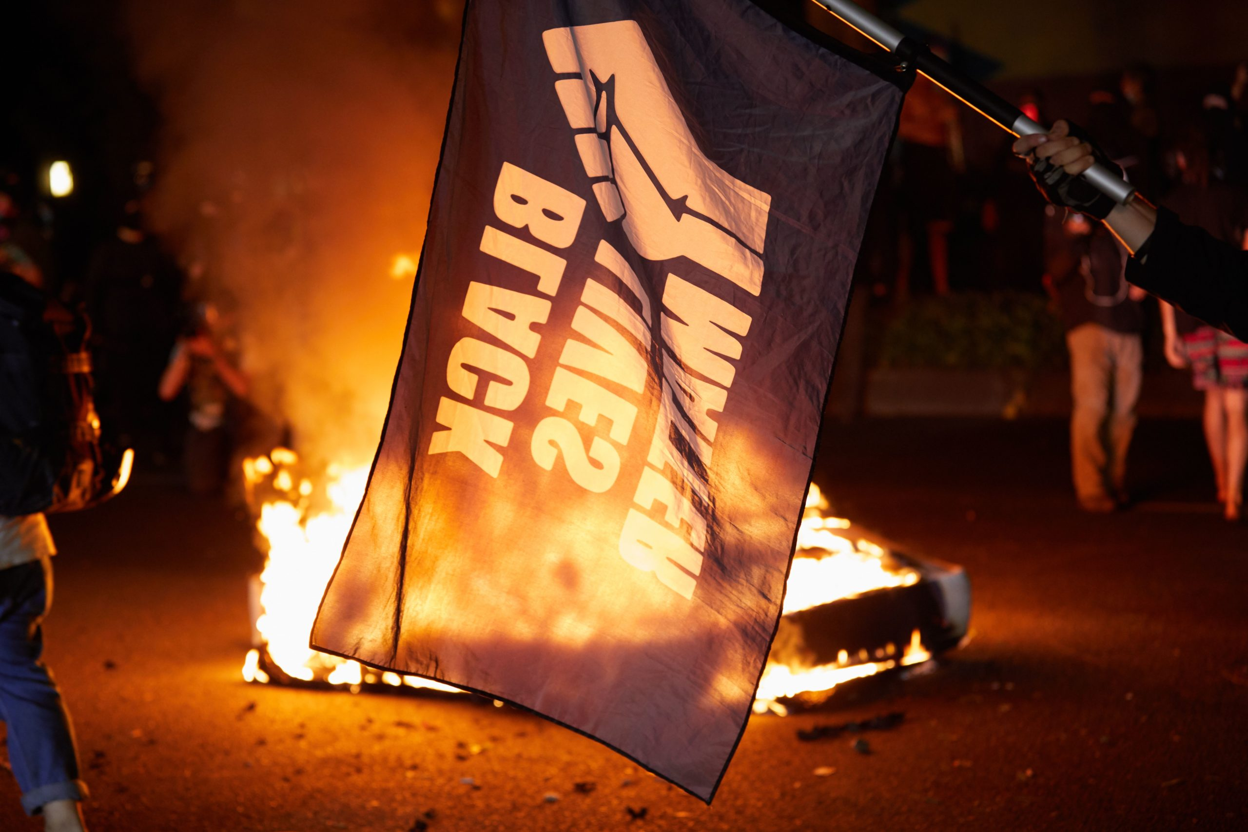 A Black Lives Matter flag waves in front of a fire at the North Precinct Police building in Portland, Oregon on September 6, 2020. - Protestors are marching for an end to racial inequality and police violence. Aaron Danielson, 39, a supporter of a far-right group called Patriot Prayer, was fatally shot August 29, 2020, in Portland, Oregon after he joined pro-Trump supporters who descended on the western US city, sparking confrontations with Black Lives Matter counter-protesters. (Photo by Allison Dinner / AFP) (Photo by ALLISON DINNER/AFP via Getty Images)