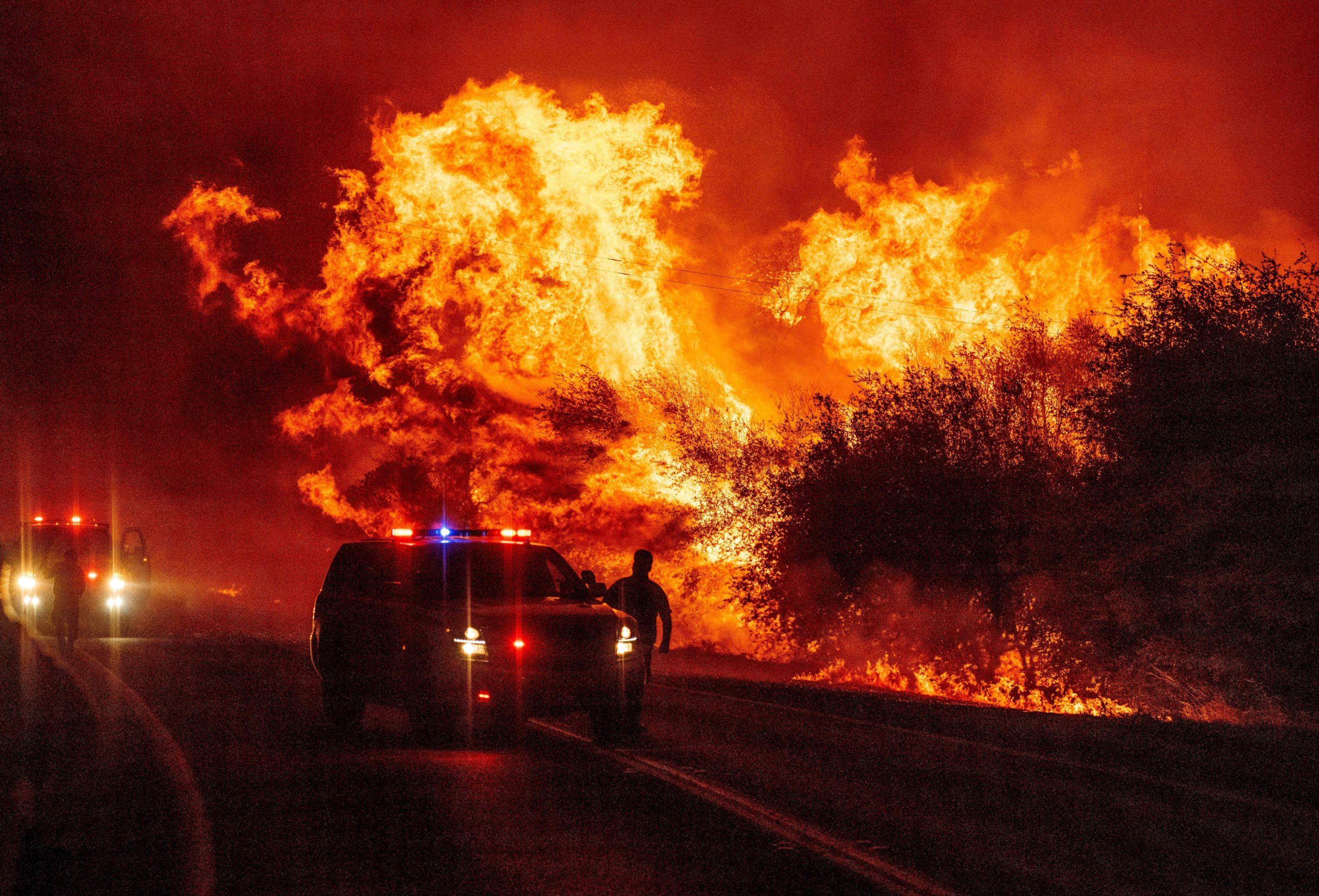 A law enforcement officer watches flames launch into the air as fire continues to spread at the Bear fire in Oroville, California on September 9, 2020. - Dangerous dry winds whipped up California's record-breaking wildfires and ignited new blazes, as hundreds were evacuated by helicopter and tens of thousands were plunged into darkness by power outages across the western United States. (Photo by JOSH EDELSON/AFP via Getty Images)