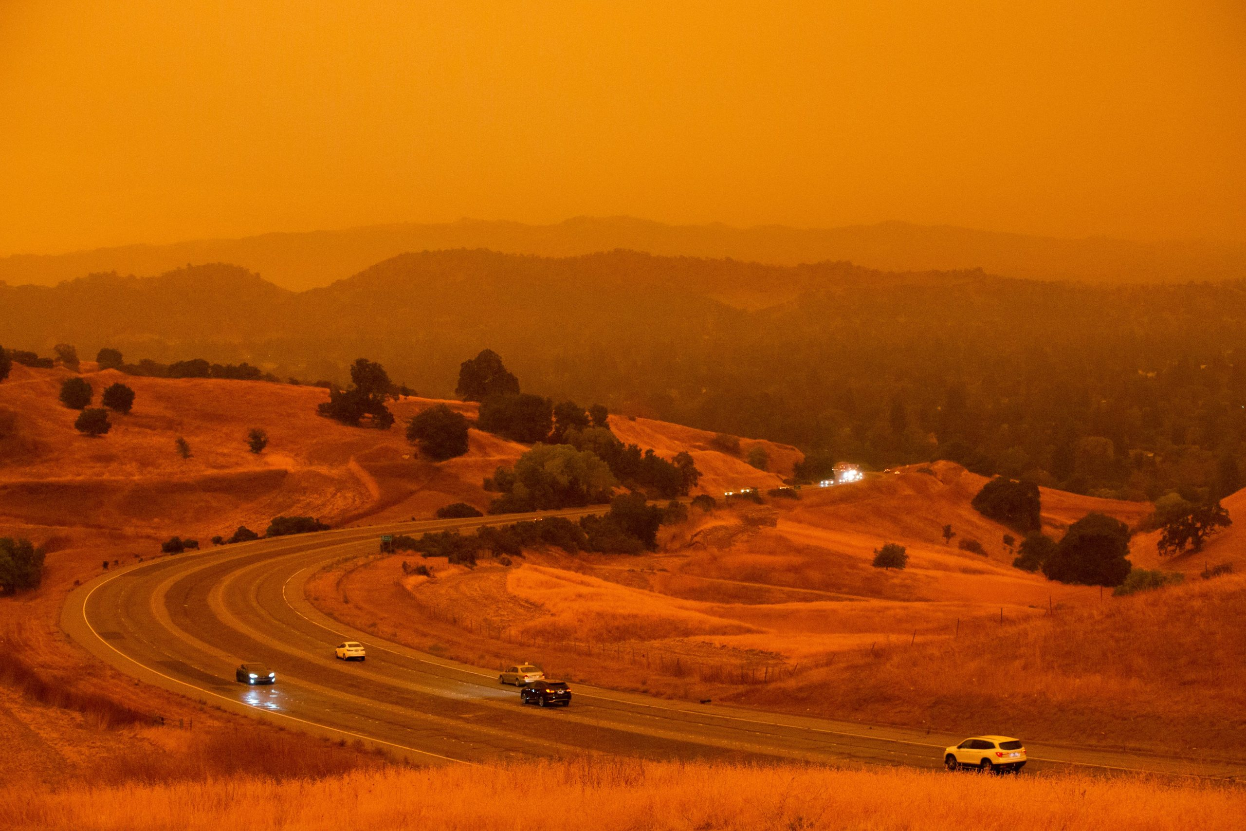 Cars drive along Ygnacio Valley Road below an orange sky filled with wildfire smoke in Concord, California on September 9, 2020, as a hazy-looking Walnut Creek can be seen in the distance through the smoke. - Dangerous dry winds whipped up California's record-breaking wildfires and ignited new blazes, as hundreds were evacuated by helicopter and tens of thousands were plunged into darkness by power outages across the western United States. (Photo by BRITTANY HOSEA-SMALL/AFP via Getty Images)