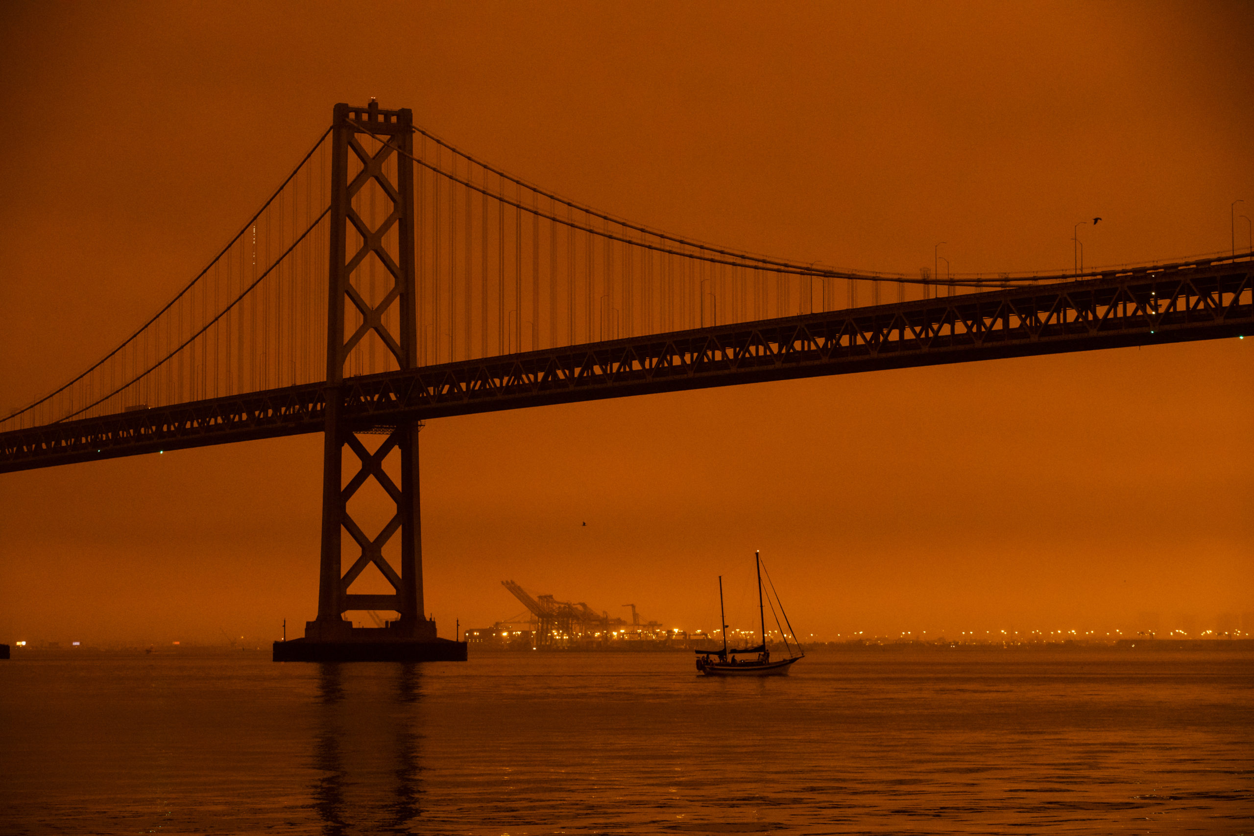 SAN FRANCISCO, CA - SEPTEMBER 09: A ship passes beneath the Bay Bridge as smoke from various wildfires burning across Northern California mixes with the marine layer, blanketing San Francisco in darkness and an orange glow on September 9, 2020 in San Francisco, California. Over 2 million acres have burned this year as wildfires continue to burn across the state. (Photo by Philip Pacheco/Getty Images)