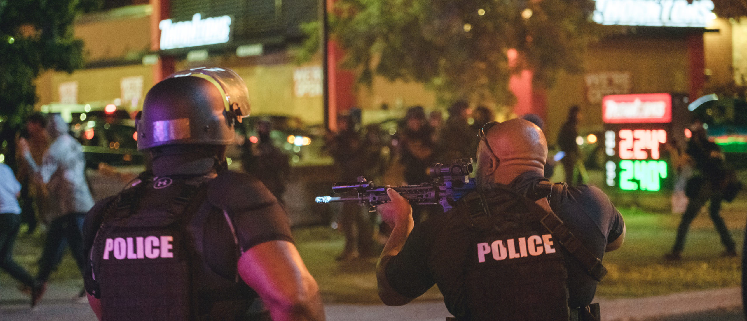 LOUISVILLE, KY - SEPTEMBER 23: A police officer takes aim at protesters shortly after shots are fired at police, resulting in two injured officers, on September 23, 2020 in Louisville, Kentucky. Protesters took to streets after Kentucky Attorney General Daniel Cameron's announcement to indict only one of the three LMPD officers involved in the death of Breonna Taylor during a no-knock raid executed on her apartment on March 13, 2020. (Photo by Jon Cherry/Getty Images)