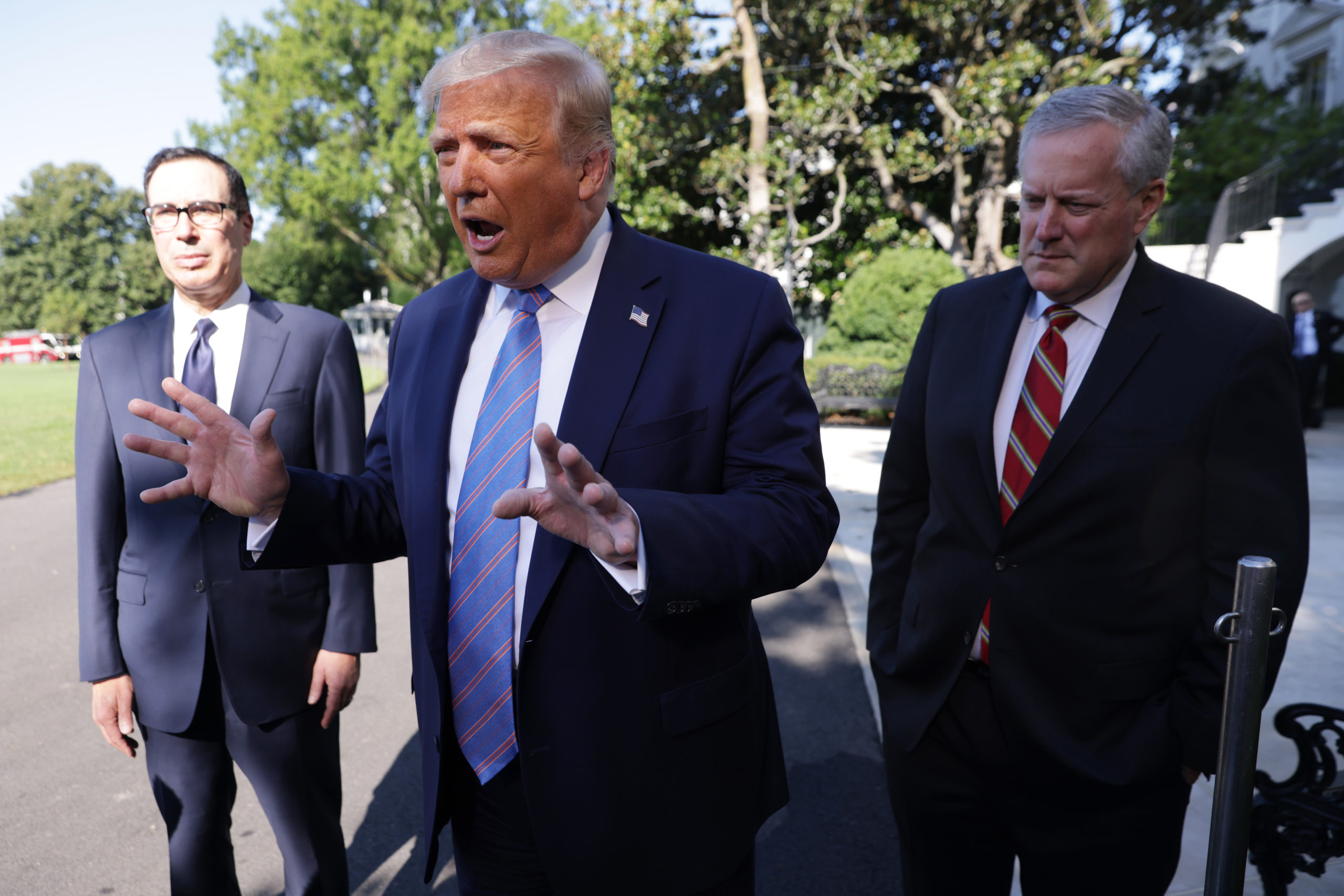 WASHINGTON, DC - JULY 29: U.S. President Donald Trump speaks as Secretary of Treasury Steven Mnuchin (L) and White House Chief of Staff Mark Meadows (R) listen prior to Trump's Marine One departure from the South Lawn of the White House July 29, 2020 in Washington, DC. President Trump is traveling to visit the Double Eagle Energy oil rig in Midland, Texas, and will attend a fundraising luncheon for the Republican Party and his reelection campaign. (Photo by Alex Wong/Getty Images)