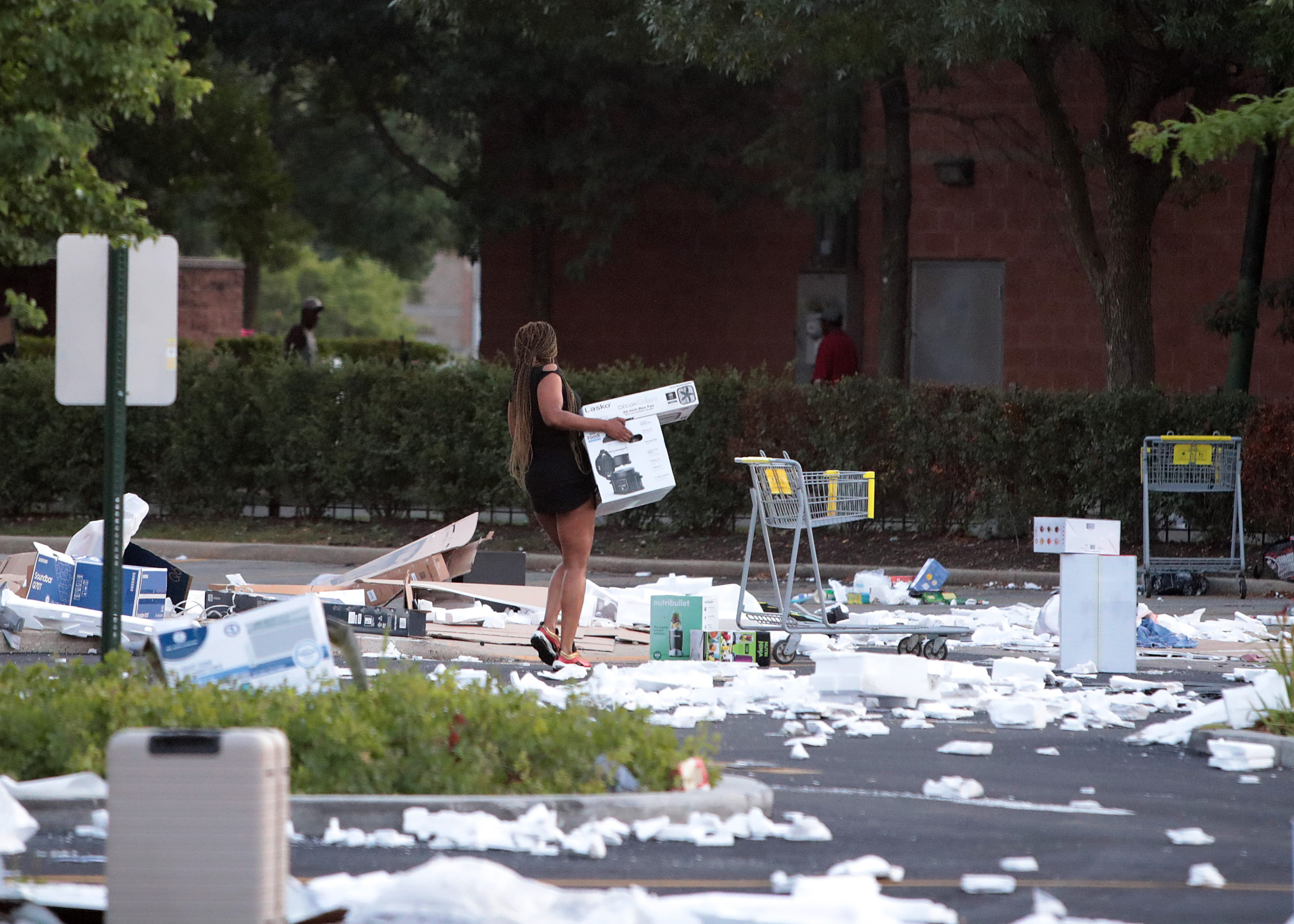 CHICAGO, ILLINOIS - AUGUST 10: A person carries a box near a looted Best Buy store seen after parts of the city had widespread looting and vandalism, on August 10, 2020 in Chicago, Illinois. Police made several arrests during the night of unrest and recovered at least one firearm. (Scott Olson/Getty Images)