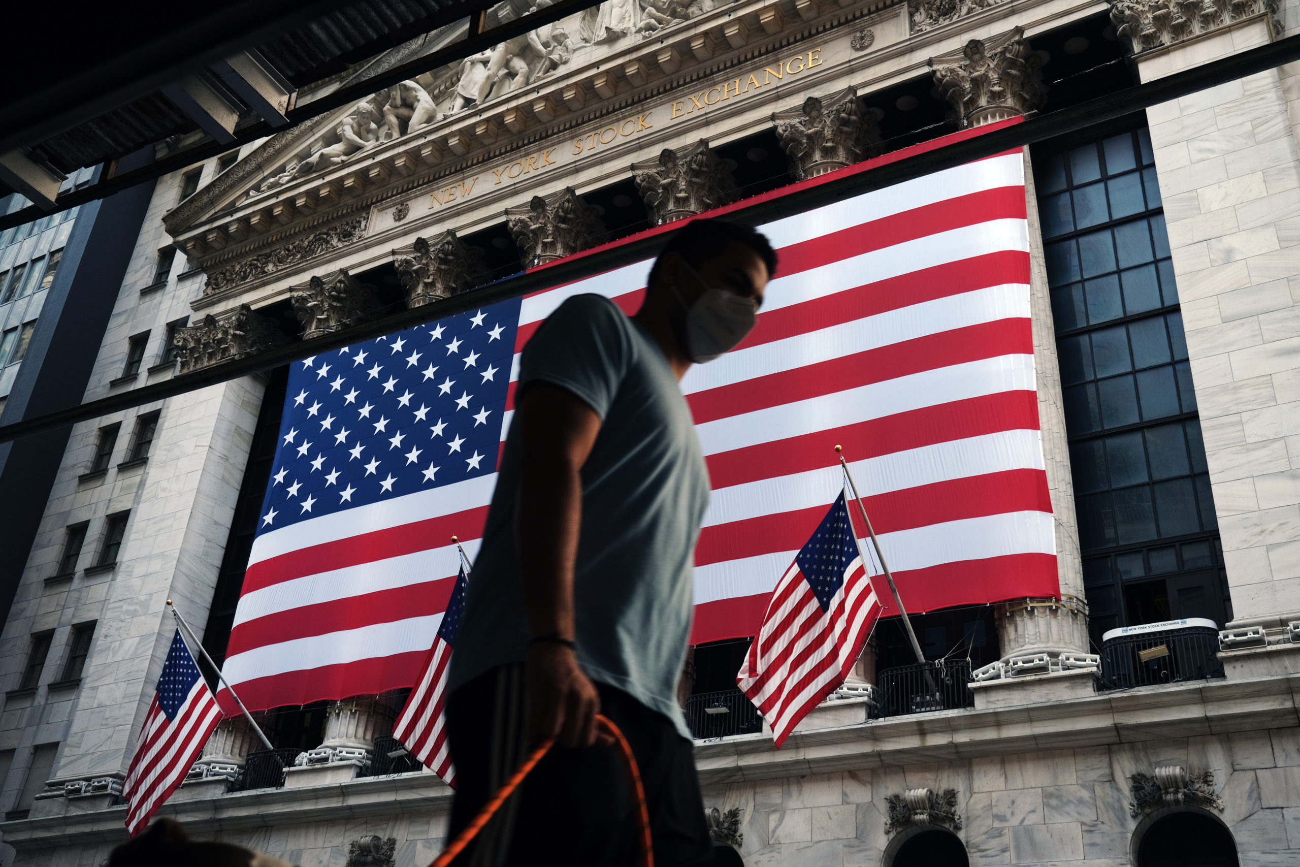 People walk by the New York Stock Exchange in New York City. (Spencer Platt/Getty Images)