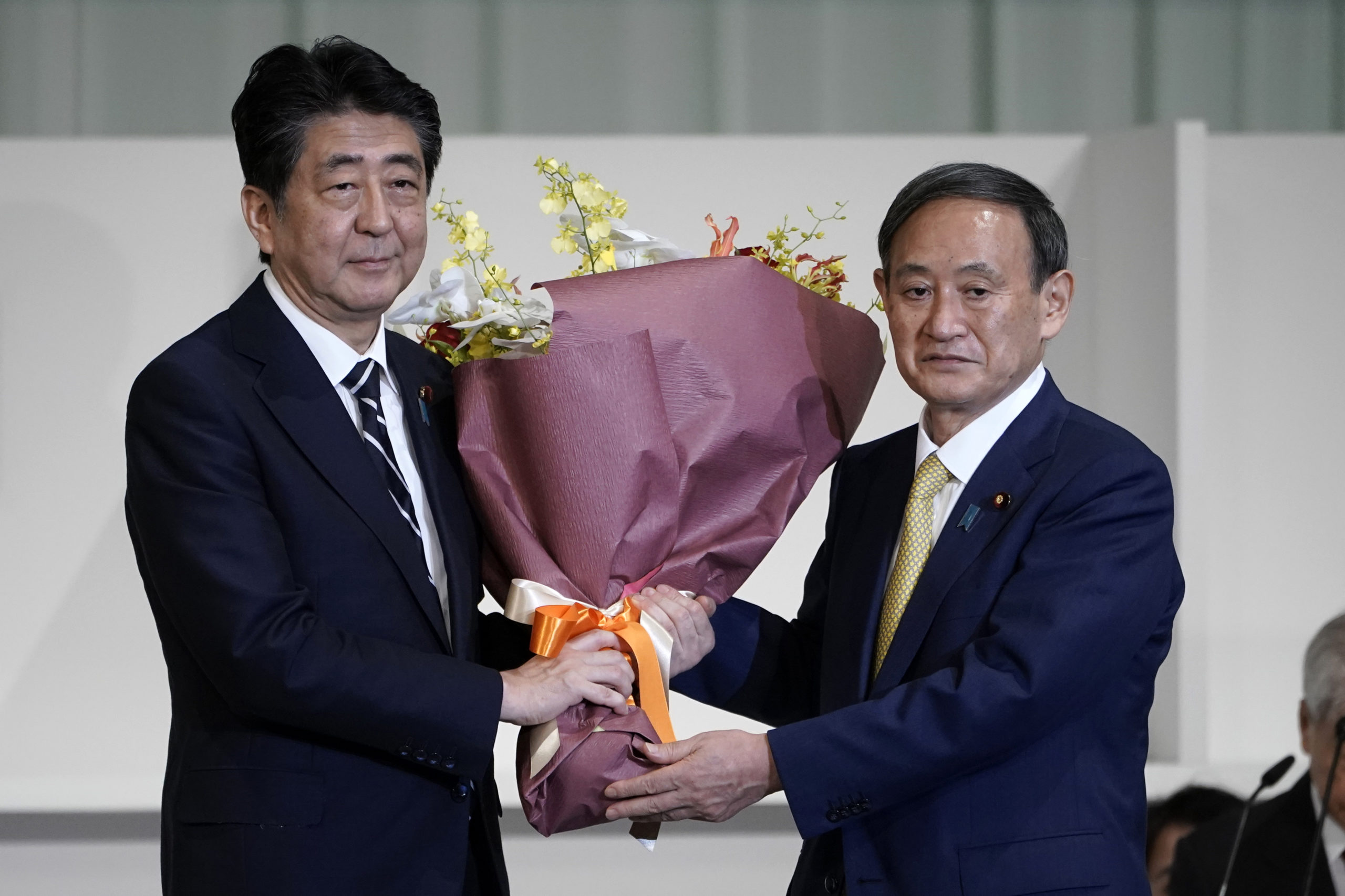 TOKYO, JAPAN - SEPTEMBER 14: Chief Cabinet Secretary Yoshihide Suga (R) presents flowers to Japan's Prime Minister Shinzo Abe after Suga was elected as new head of Japan's ruling party at the Liberal Democratic Party's (LDP) leadership election on September 14, 2020 in Tokyo, Japan. (Photo by Eugene Hoshiko - Pool/Getty Images)