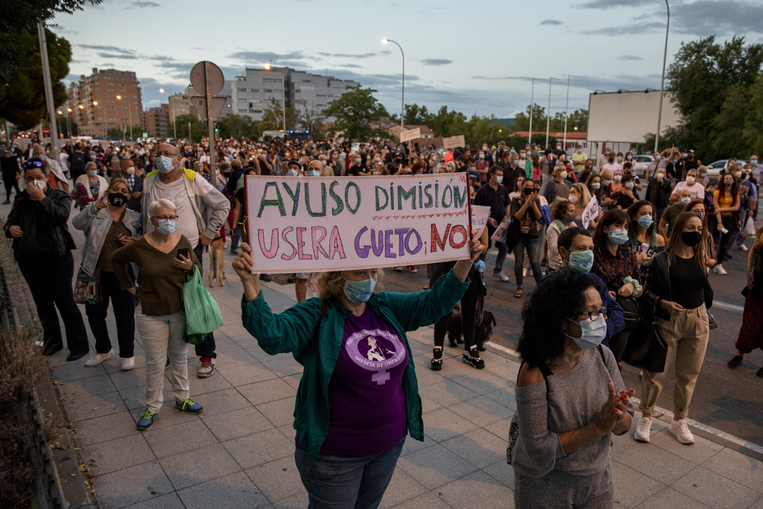 A protester wearing protective masks holds a placard reading 'Ayuso resignation. Usera is not a ghetto' amid other protesters during a demonstration, in the Usera neighborhood, against the measures imposed by the Madrid regional government on areas with the most COVID-19 cases on September 20, 2020 in Madrid, Spain. Spain is the midst of a second wave of COVID-19, reporting more than 122,000 new cases in the last two weeks. More than a third are in the Madrid region. (Photo by Pablo Blazquez Dominguez/Getty Images)