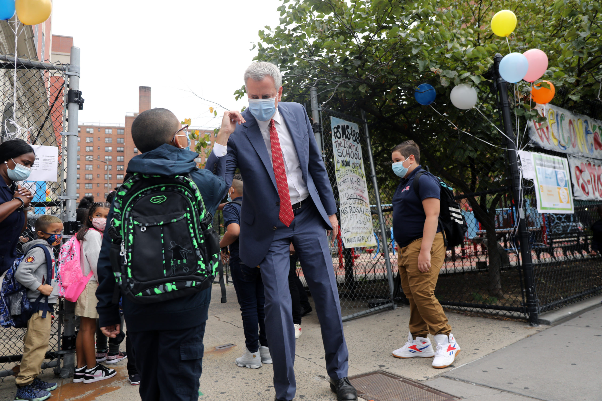 New York City Mayor Bill de Blasio elbow bumps a student at P.S. 188 as he welcomes elementary school students back to the city's public schools for in-person learning on Tuesday. (Spencer Platt/Getty Images)