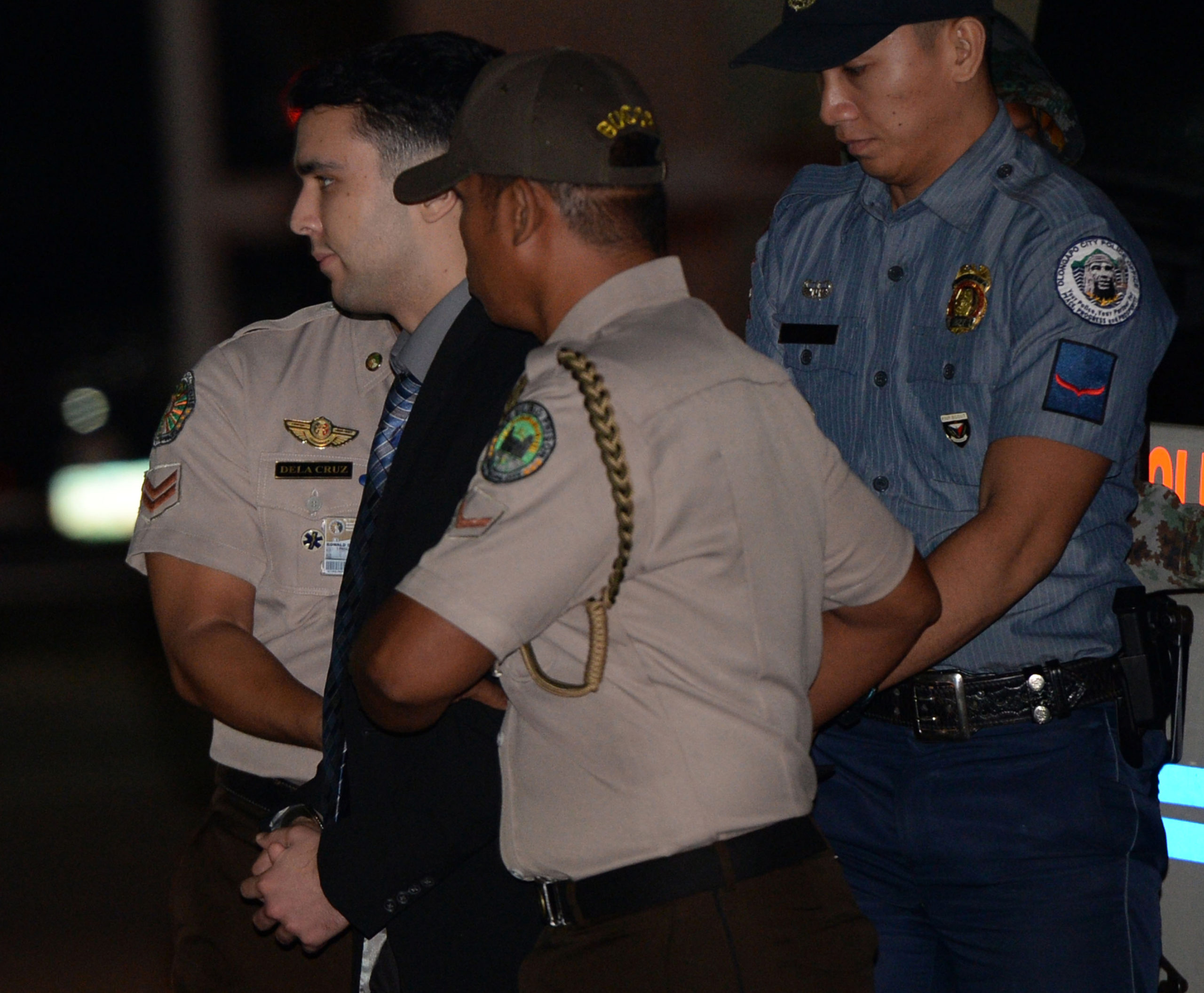 US Marine Lance Corporal Joseph Scott Pemberton (C) is escorted by a policeman and bureau of corrections official shortly after arriving at Camp Aguinaldo in Quezon City on December 1, 2015, from Olongapor city where a court convicted of him of homicide for the killing of Jennifer Laude in a motel in October 2014. A Philippine court has convicted a US Marine of killing a Filipina transgender woman in a red light district, in a case that reignited long-simmering anti-US sentiment in the country. AFP PHOTO / TED ALJIBE / POOL / AFP / POOL / TED ALJIBE (Photo credit should read TED ALJIBE/AFP via Getty Images)