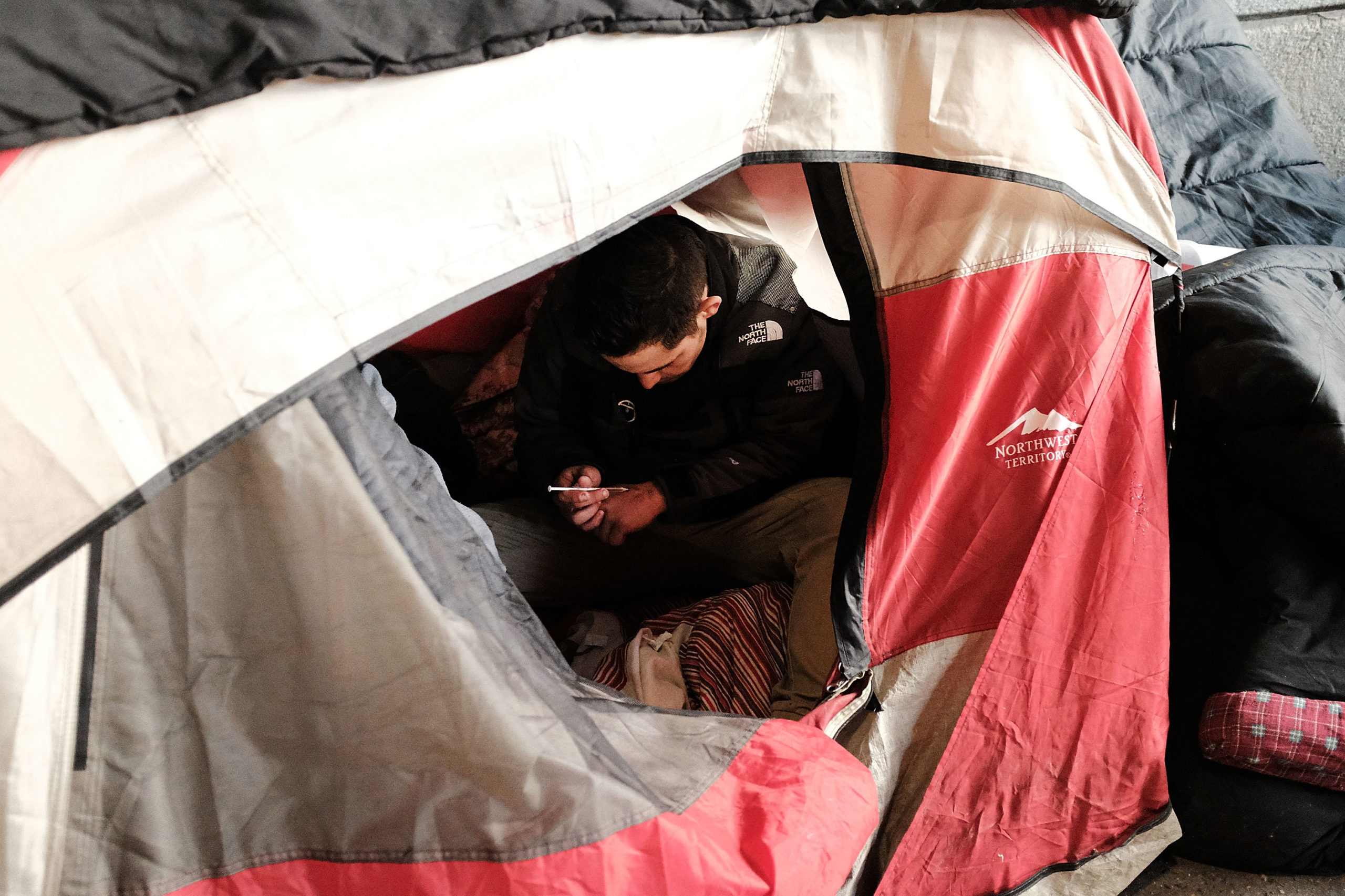 A man uses heroin in a tent under a bridge where he lives with other addicts in 2018 in Philadelphia, Pennsylvania. (Spencer Platt/Getty Images)