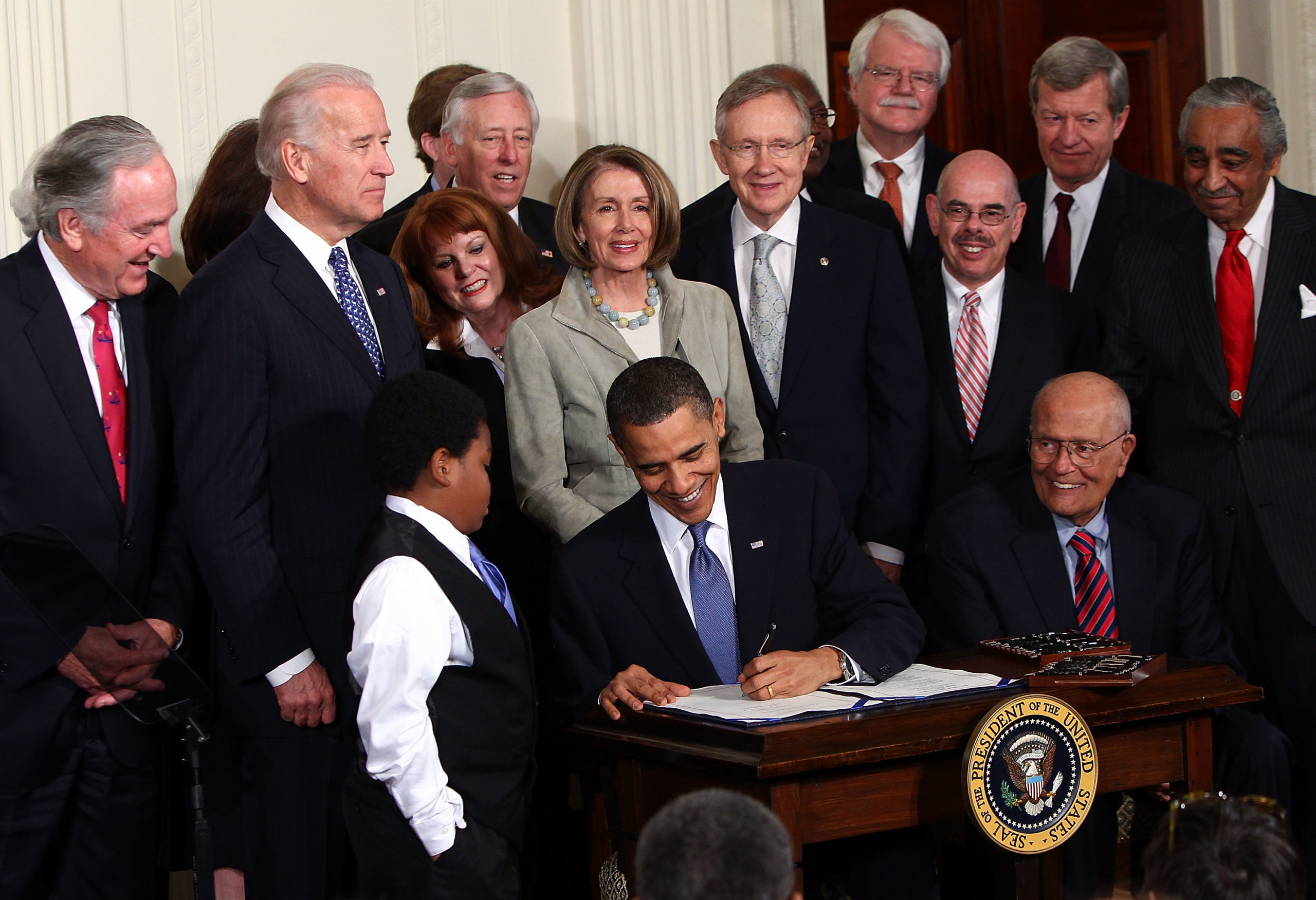 Former U.S. president Barack Obama signs the Affordable Health Care for America Act during a ceremony with fellow Democrats in the East Room of the White House March 23, 2010 in Washington, DC. (Win McNamee/Getty Images)