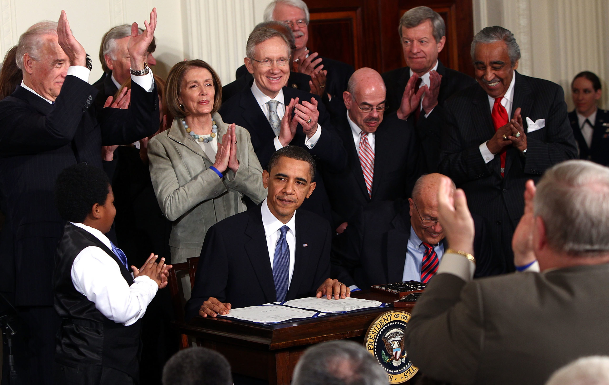 Former President Barack Obama is applauded after signing the Affordable Health Care Act during a ceremony with fellow Democrats in the East Room of the White House March 23, 2010. (Win McNamee/Getty Images)