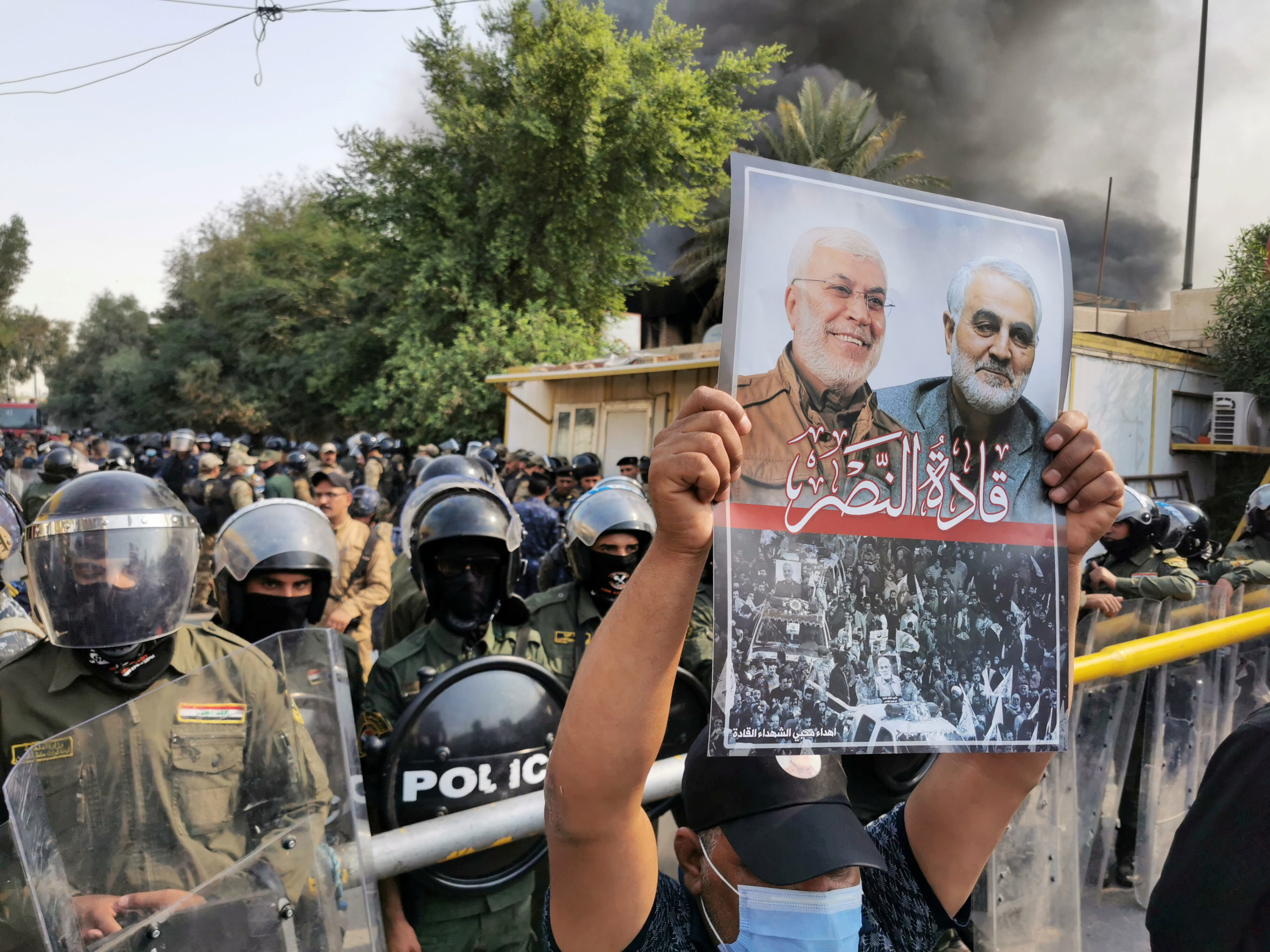 A supporter of Hashid Shaabi (Popular Mobilization Forces) holds a picture of late Iran's Quds Force top commander Qassem Soleimani and Iraqi militia commander Abu Mahdi al-Muhandis who were killed in a U.S. airstrike during a protest in Baghdad, Iraq October 17, 2020. REUTERS/ Thaier Al-Sudani