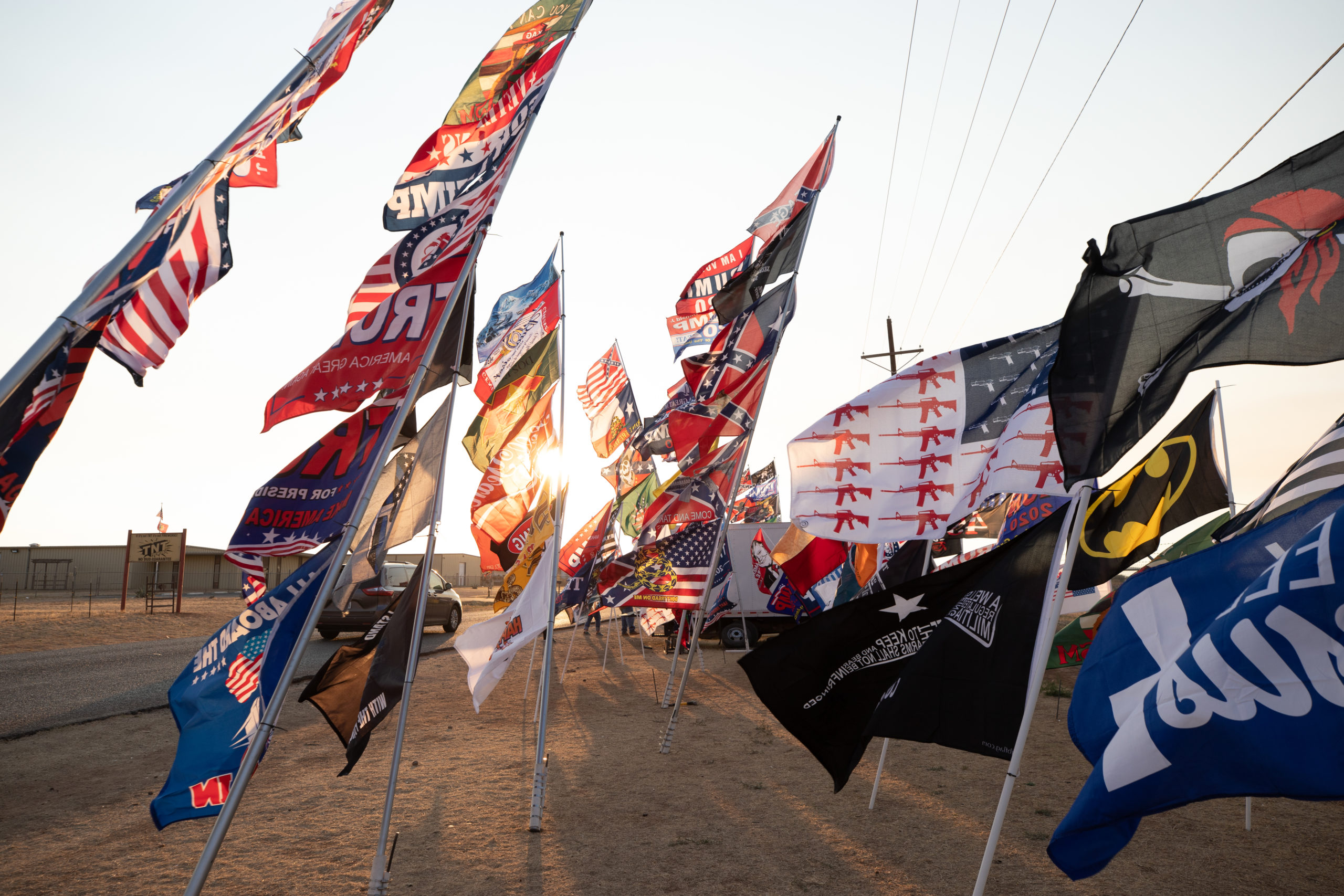 """Flags fly outside Cooks Garage, the meeting place of hundreds of President Donald Trump supporters after a """"Trump Train"""" car parade in Lubbock, Texas, on Sunday, Oct. 18, 2020. (Kaylee Greenlee - DCNF)"""