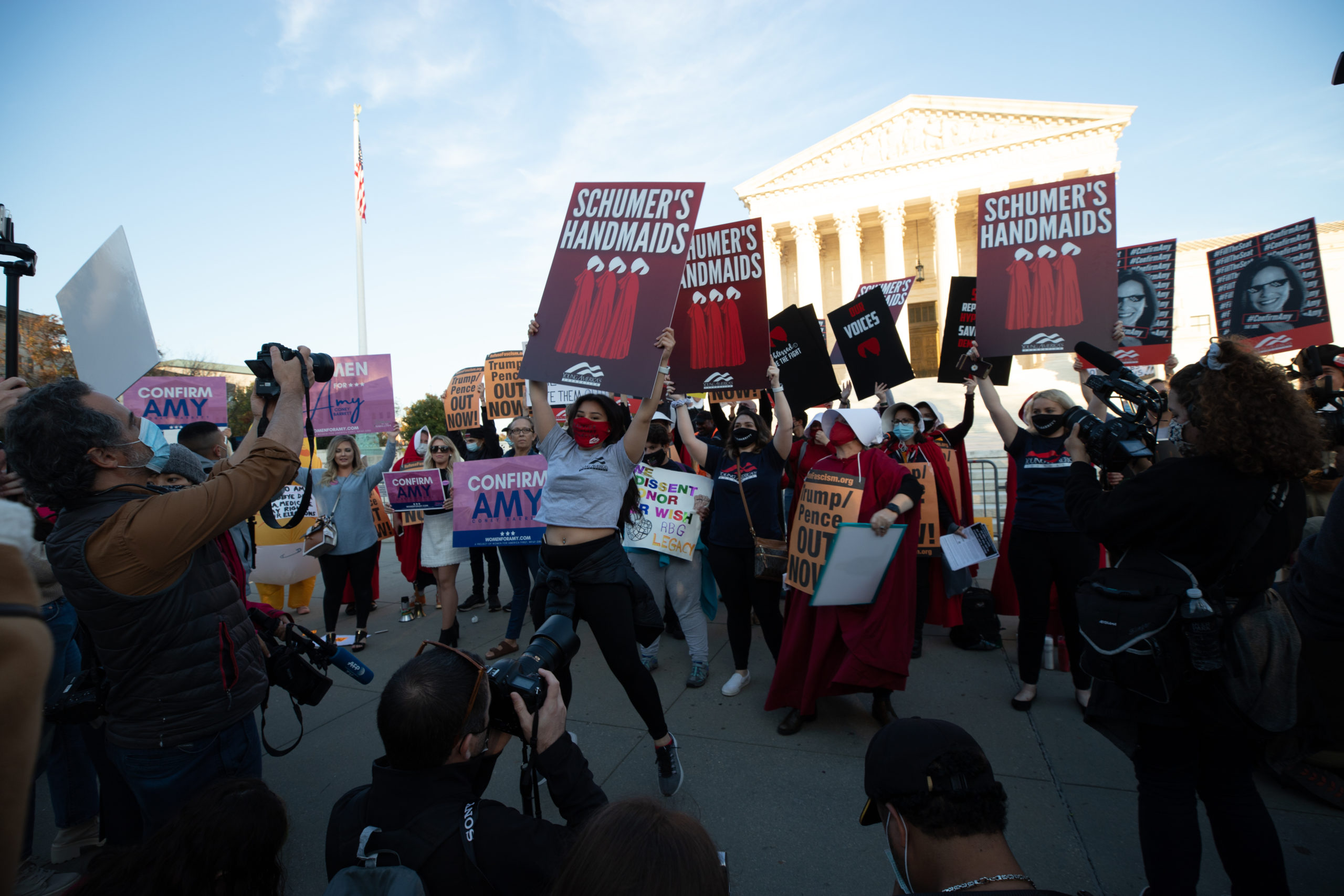A woman with Young America's Foundation jumps in front of anti-Amy Coney Barrett and anti-Trump protesters at the Supreme Court in Washington, D.C. on October 26, 2020. (Kaylee Greenlee - Daily Caller News Foundation)
