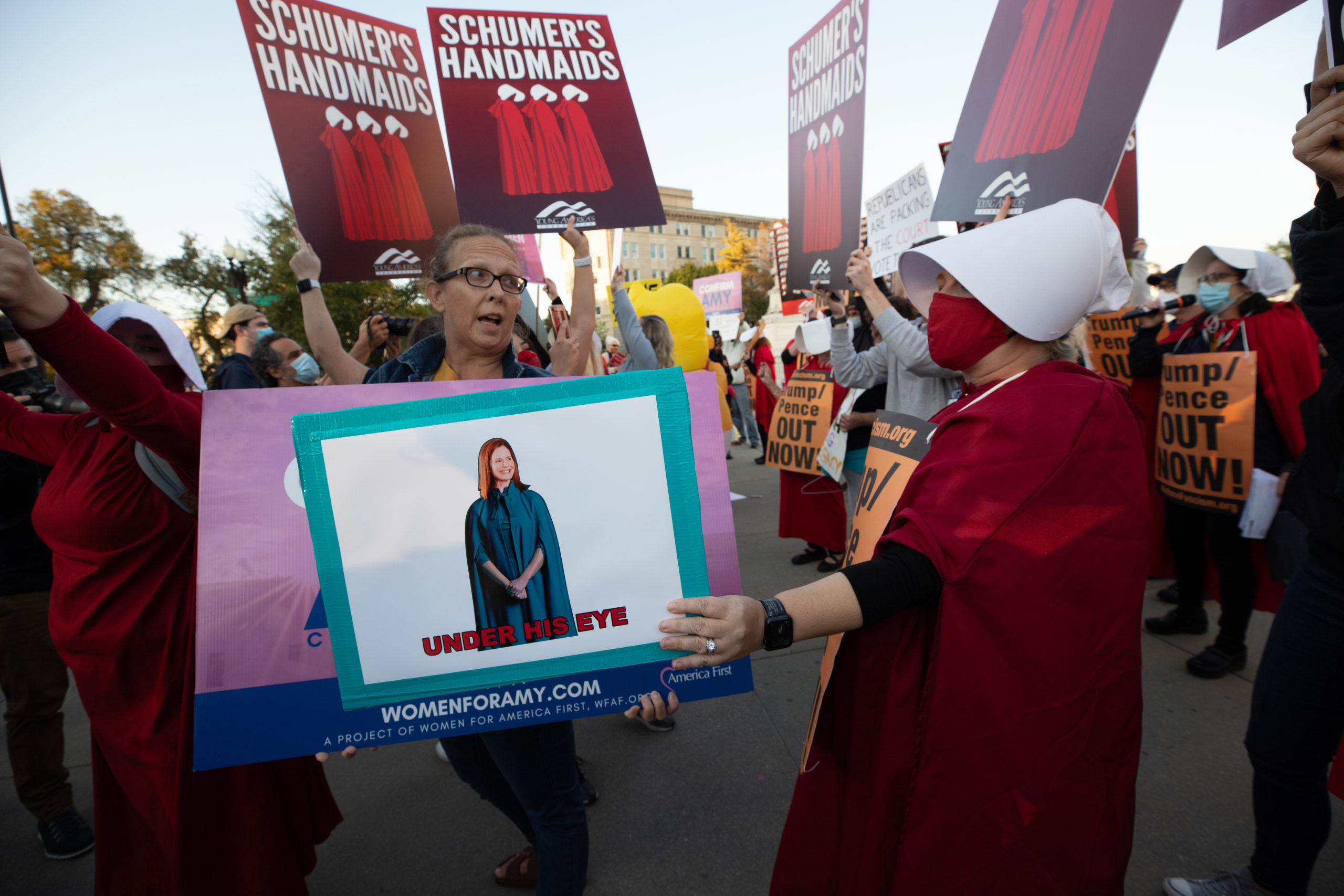 An anti-Amy Coney Barrett protester dressed as a handmaid blocks the sign of an Amy Coney Barrett supporter in Washington, D.C. on October 26, 2020. (Kaylee Greenlee - Daily Caller News Foundation)