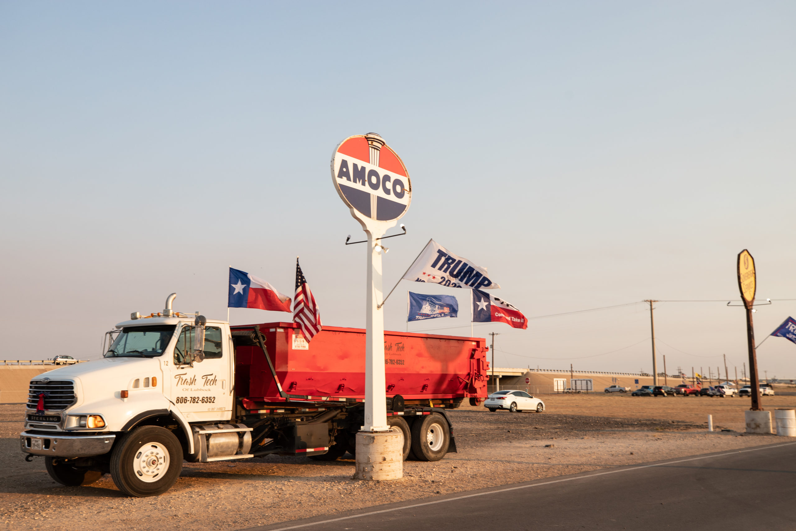 """A truck with Texas, American, and """"Trump train"""" flags returned to Cook's Garage after a """"Trump Train"""" car parade in Lubbock, Texas, on Sunday, Oct. 18, 2020. (Kaylee Greenlee - DCNF)"""