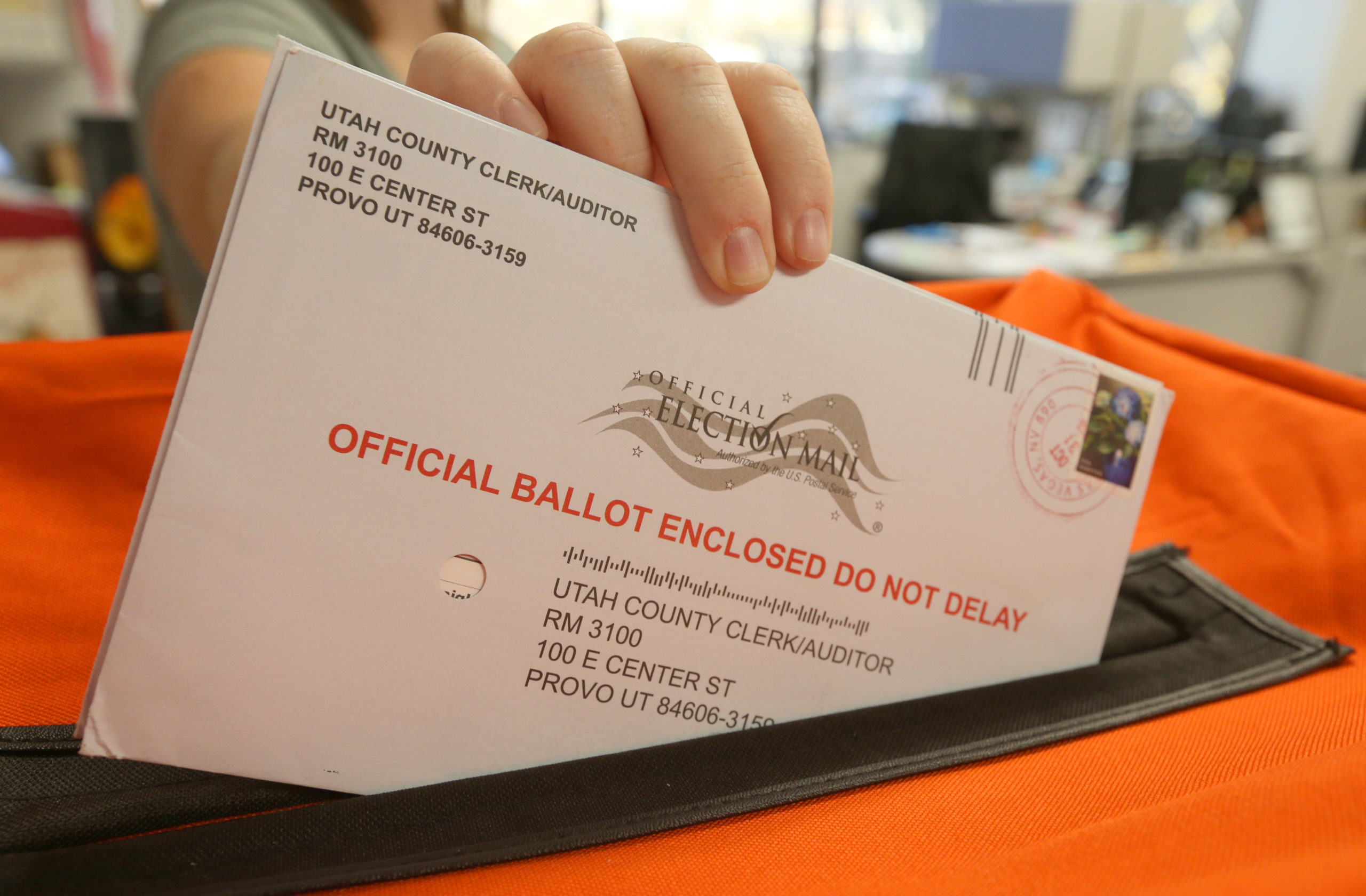 An employee at the Utah County Election office puts mail-in ballots into a container. (George Frey/Getty Images)