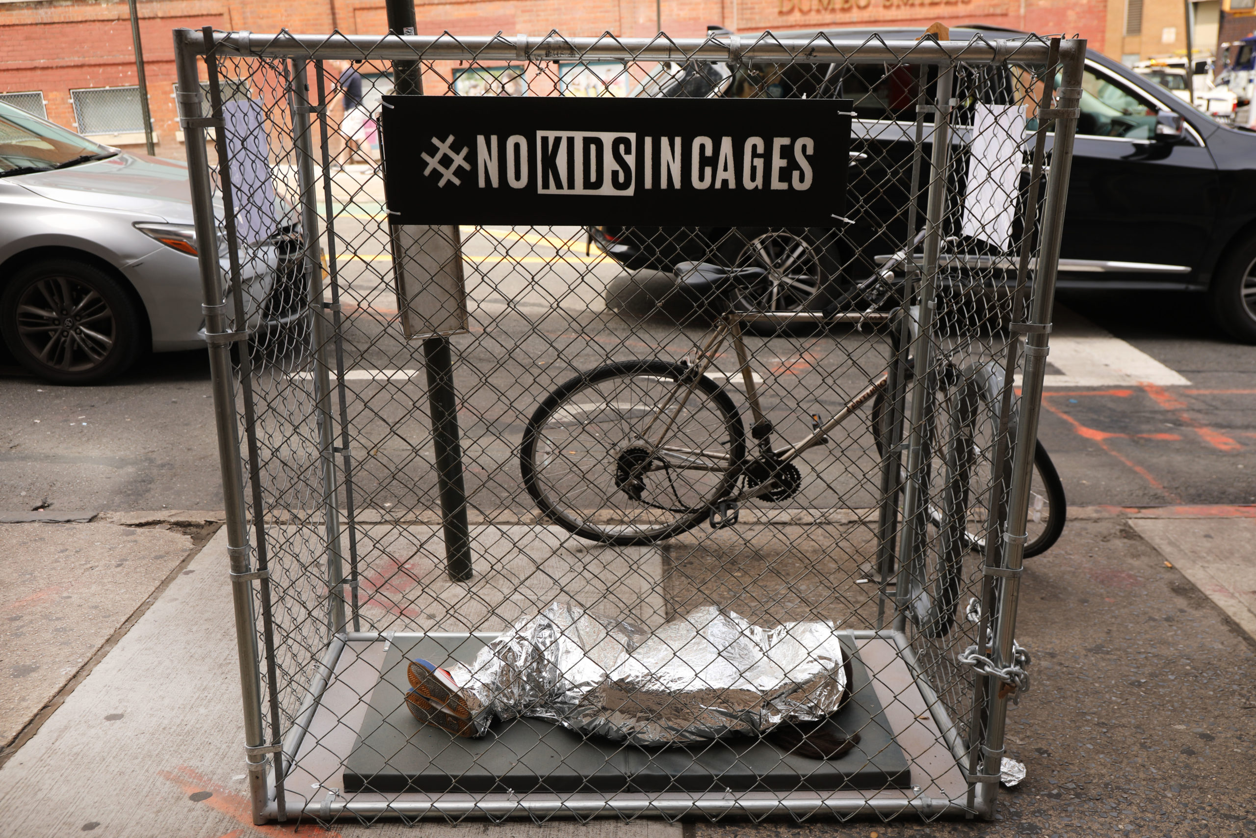 NEW YORK, NEW YORK - JUNE 12: A pop-up art installation depicting a small child curled up underneath a foil survival blanket in a chain-link cage stands along a Brooklyn street on June 12, 2019 in New York City. (Photo by Spencer Platt/Getty Images)