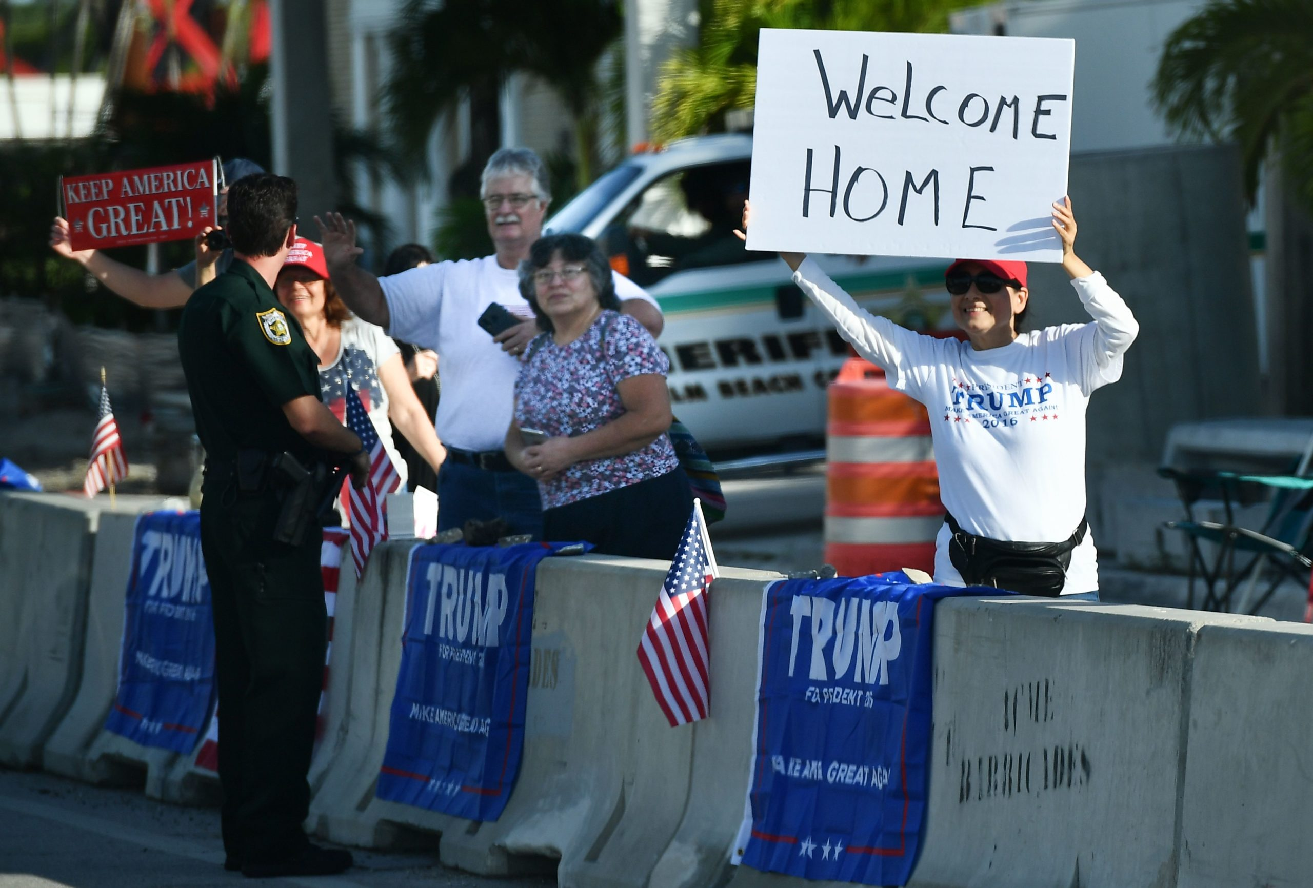 A supporter of US President Donald Trump holds up a placard in West Palm Beach, Florida near his Mar-a-Lago resort on November 27, 2019. (Photo by MANDEL NGAN / AFP) (Photo by MANDEL NGAN/AFP via Getty Images)