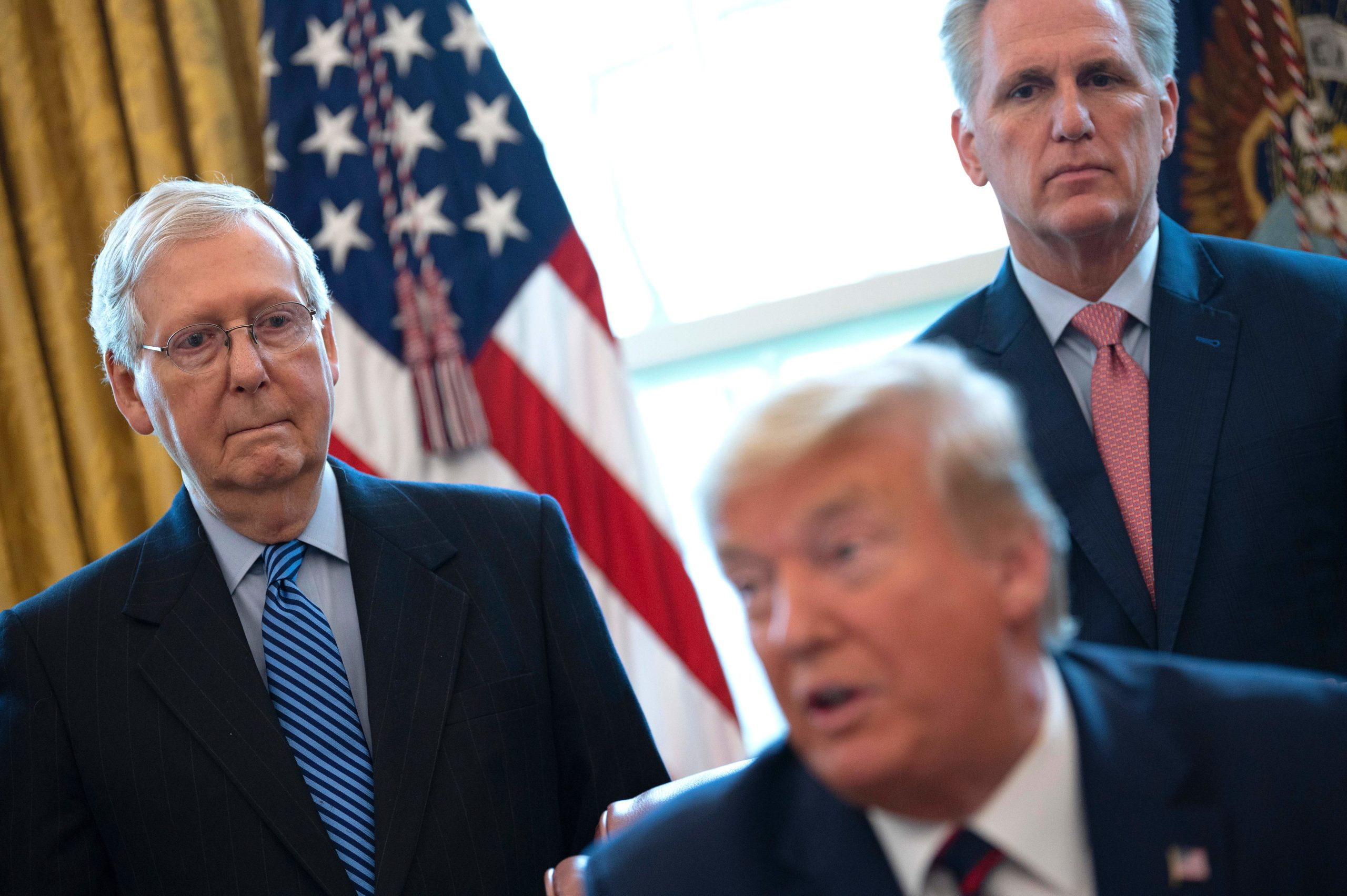 US Senate Majority Leader Mitch McConnell (L) and House Minority Leader Kevin McCarthy (R) look on as US President Donald Trump speaks before signing the CARES act, a $2 trillion rescue package to provide economic relief amid the coronavirus outbreak, at the Oval Office of the White House on March 27, 2020. - After clearing the Senate earlier this week, and as the United States became the new global epicenter of the pandemic with 92,000 confirmed cases of infection, Republicans and Democrats united to greenlight the nation's largest-ever economic relief plan. (Photo by JIM WATSON/AFP via Getty Images)