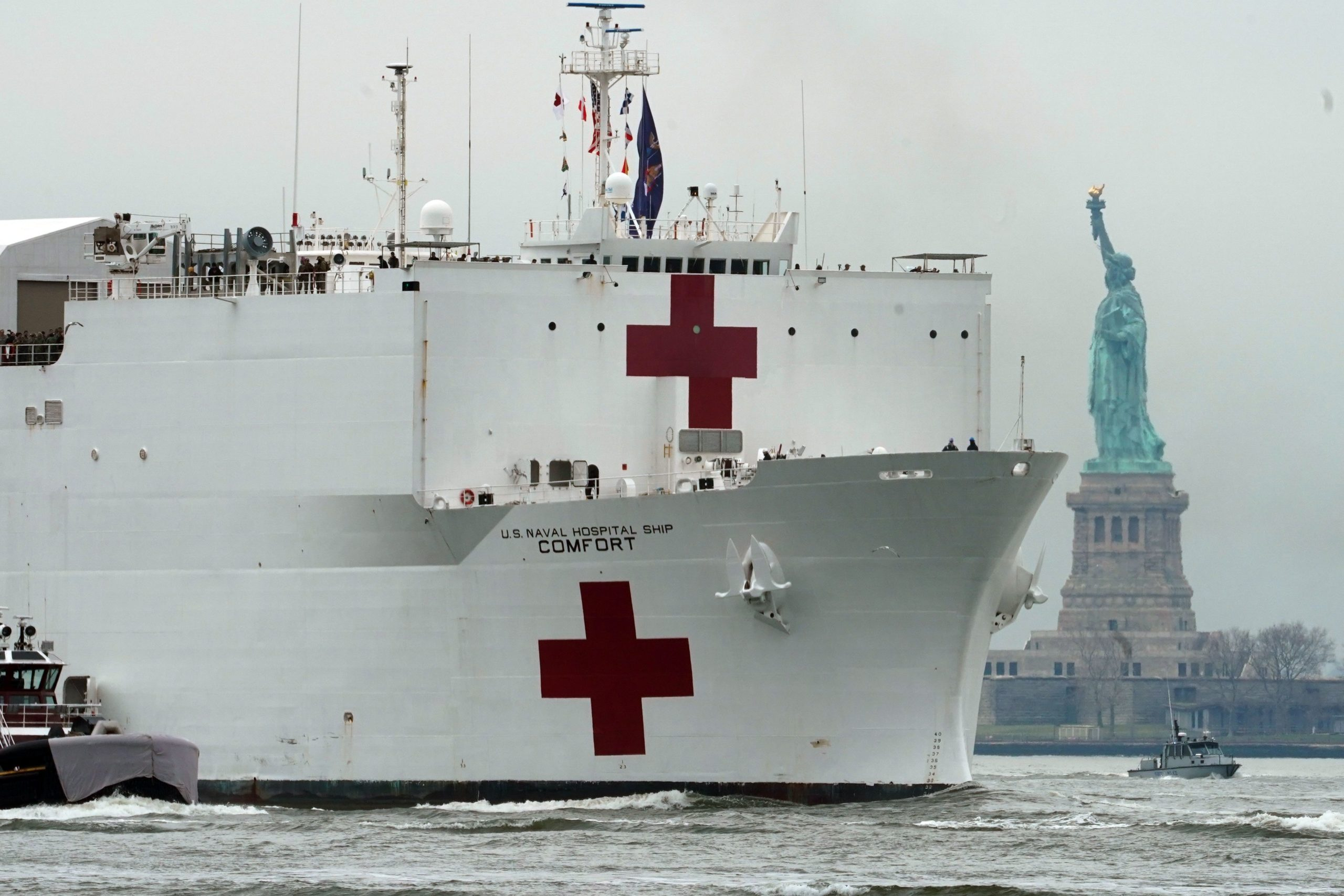 The USNS Comfort medical ship moves up the Hudson River past the Statue of Liberty as it arrives on March 30, 2020 in New York. - A military hospital ship arrived in New York Monday as America's coronavirus epicenter prepares to fight the peak of the pandemic that has killed over 2,500 people across the US. The navy's 1,000-bed USNS Comfort entered a Manhattan pier around 10:45 am (1545 GMT). It will treat non-virus-related patients, helping to ease the burden of hospitals overwhelmed by the crisis. (Photo by Bryan R. Smith / AFP) (Photo by BRYAN R. SMITH/AFP via Getty Images)