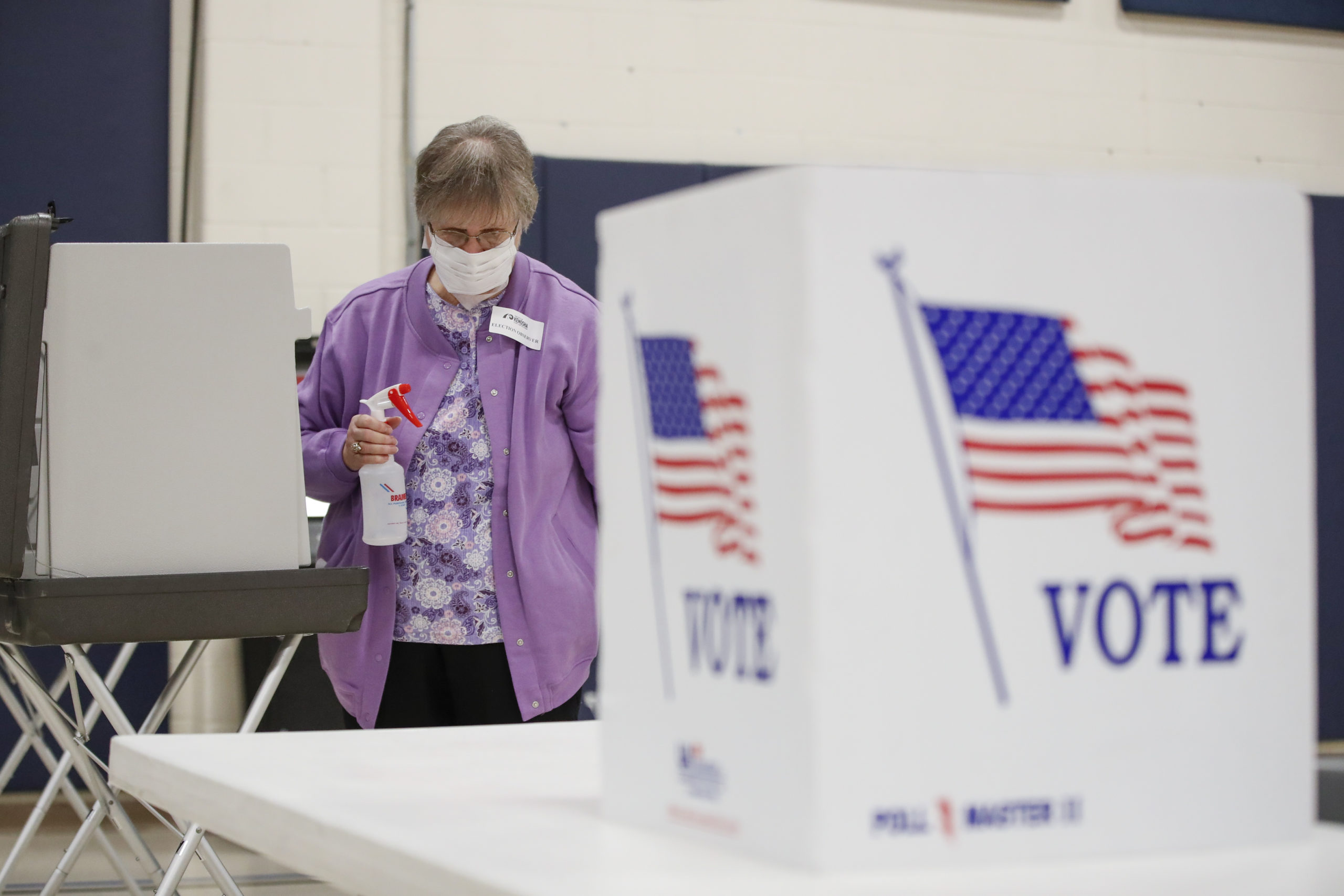 An election observer cleans voting booths in Kenosha, Wisconsin on April 7. (Kamil Krzaczynski/AFP via Getty Images)