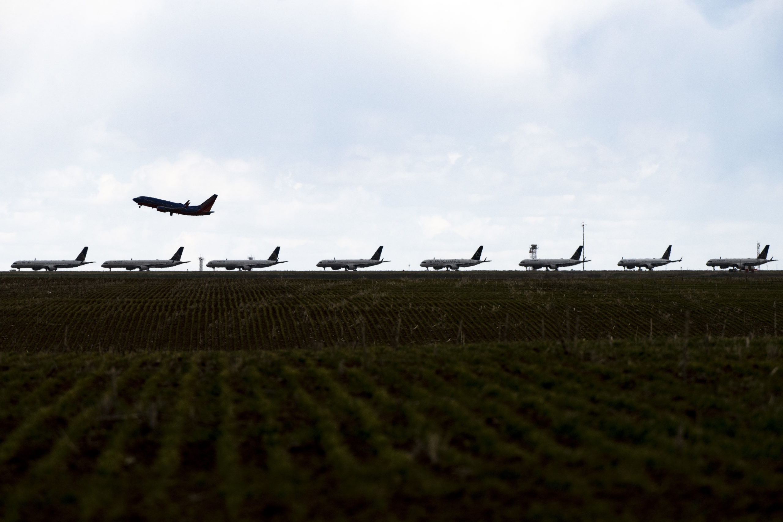 A Southwest Airlines flight takes off as United Airlines planes sit parked on a runway in Denver, Colorado as the coronavirus pandemic slows air travel. (Michael Ciaglo/Getty Images)