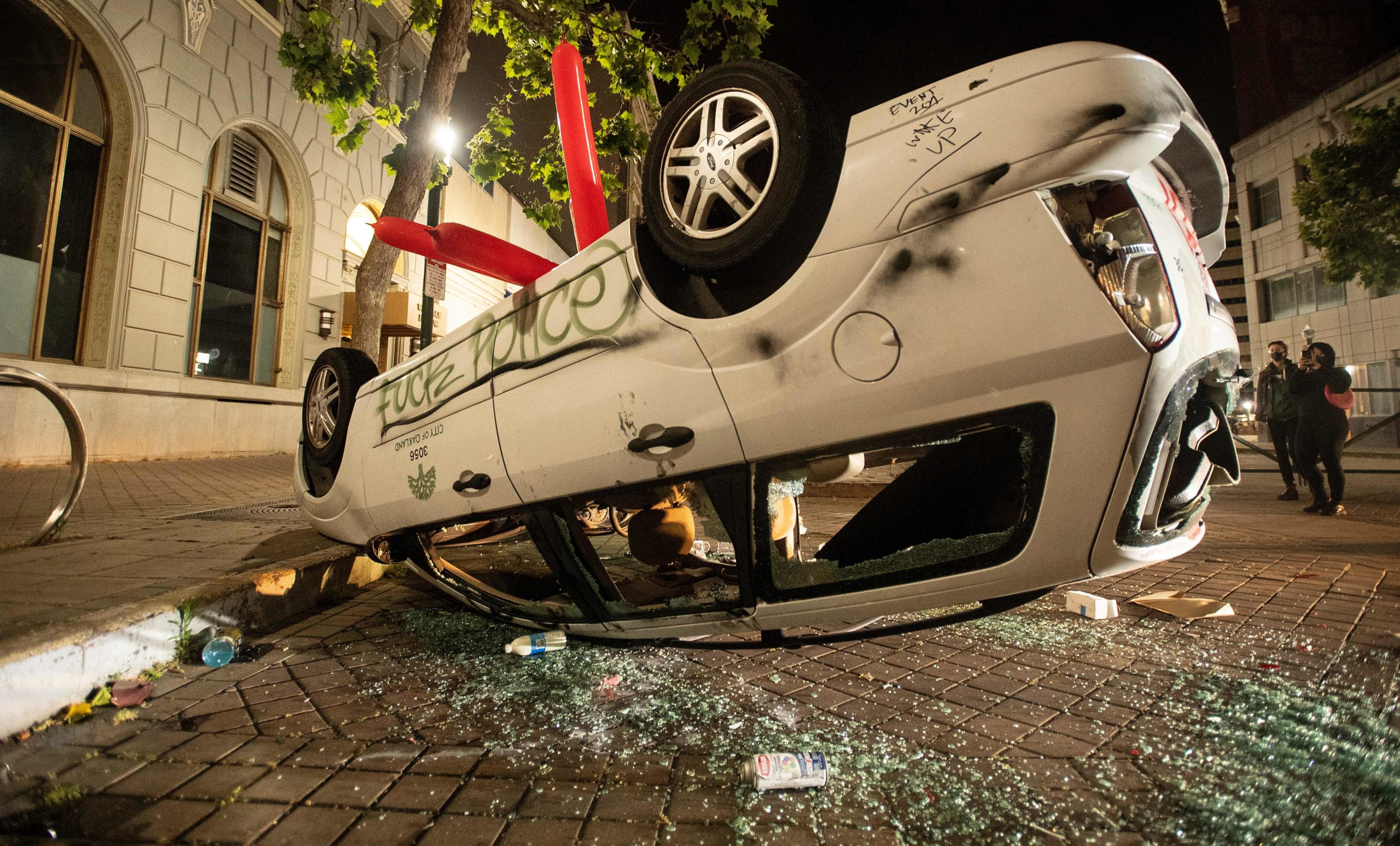 A vandalized car is flipped upside down as protesters face off against police in Oakland, California on May 29, 2020, during protests over the death of George Floyd. (Josh Edelson/AFP via Getty Images)
