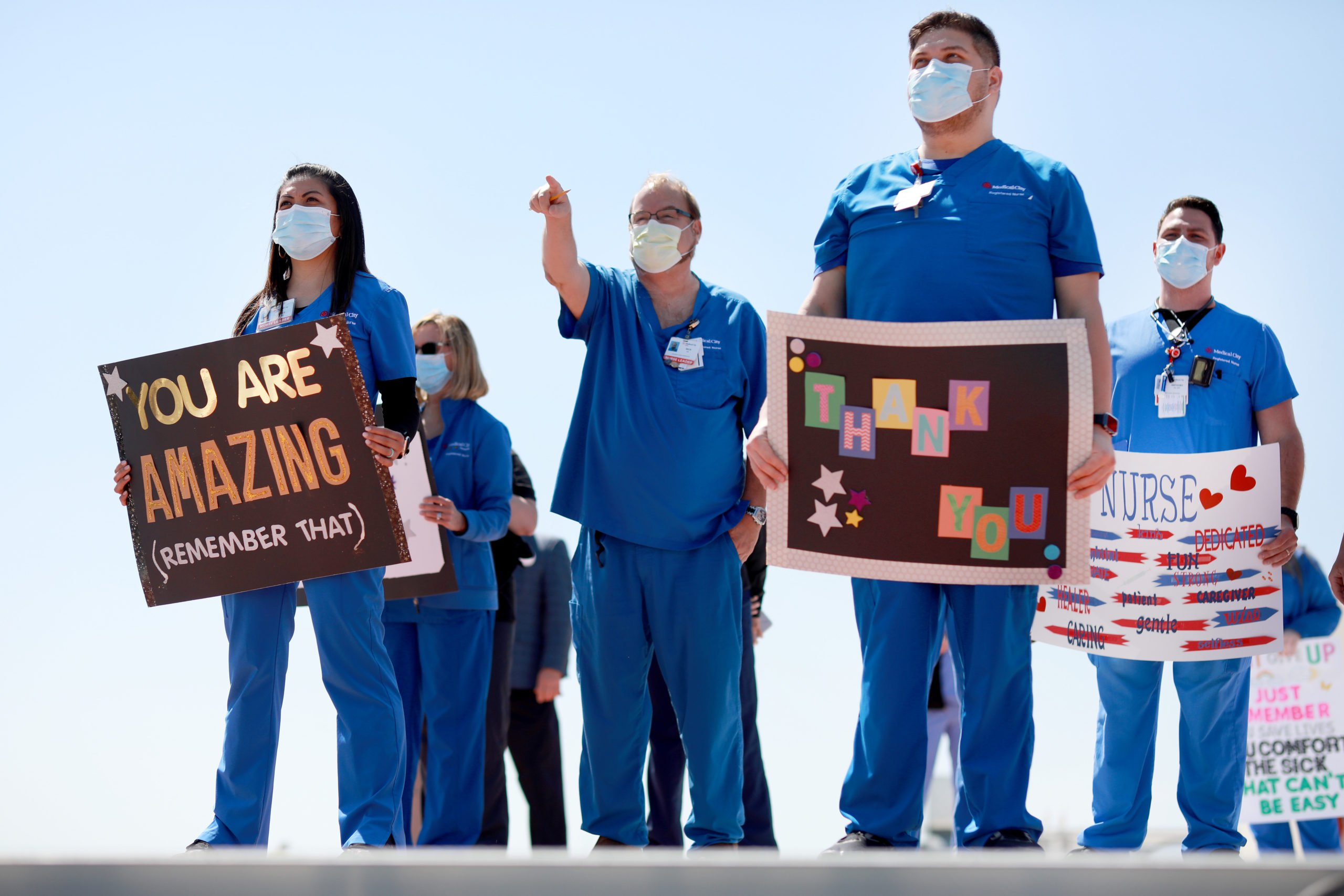 Hospital staff, including nurses, doctors and administrators, look on in anticipation of the Navy Blue Angels flyover above Medical City Dallas on May 6. (Tom Pennington/Getty Images)