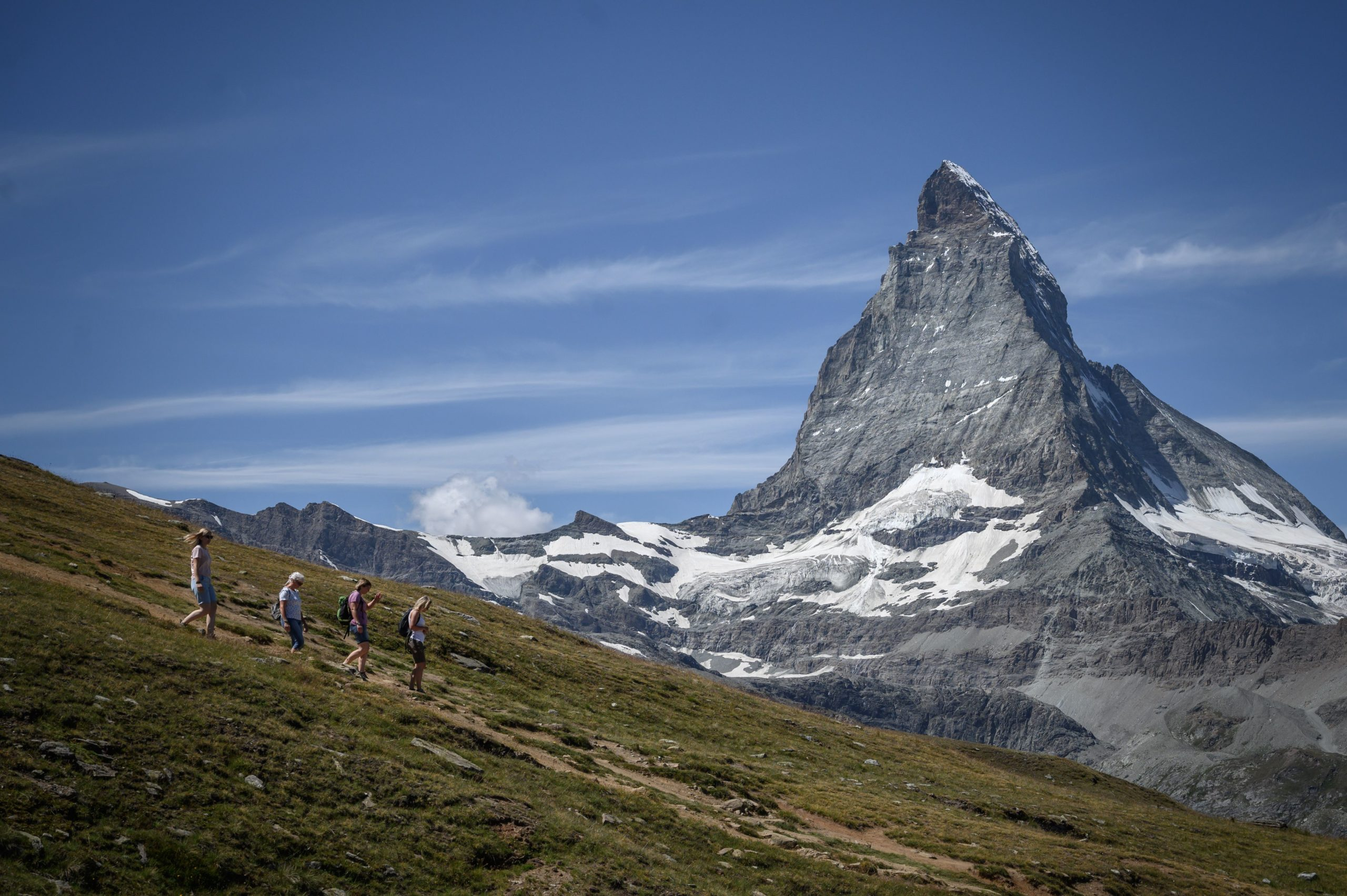 TOPSHOT - Hikers walk in front with the Matterhorn mountain in background above the resort of Zermatt as heatwave sweeps across Europe on August 8, 2020. (Photo by FABRICE COFFRINI/AFP via Getty Images)