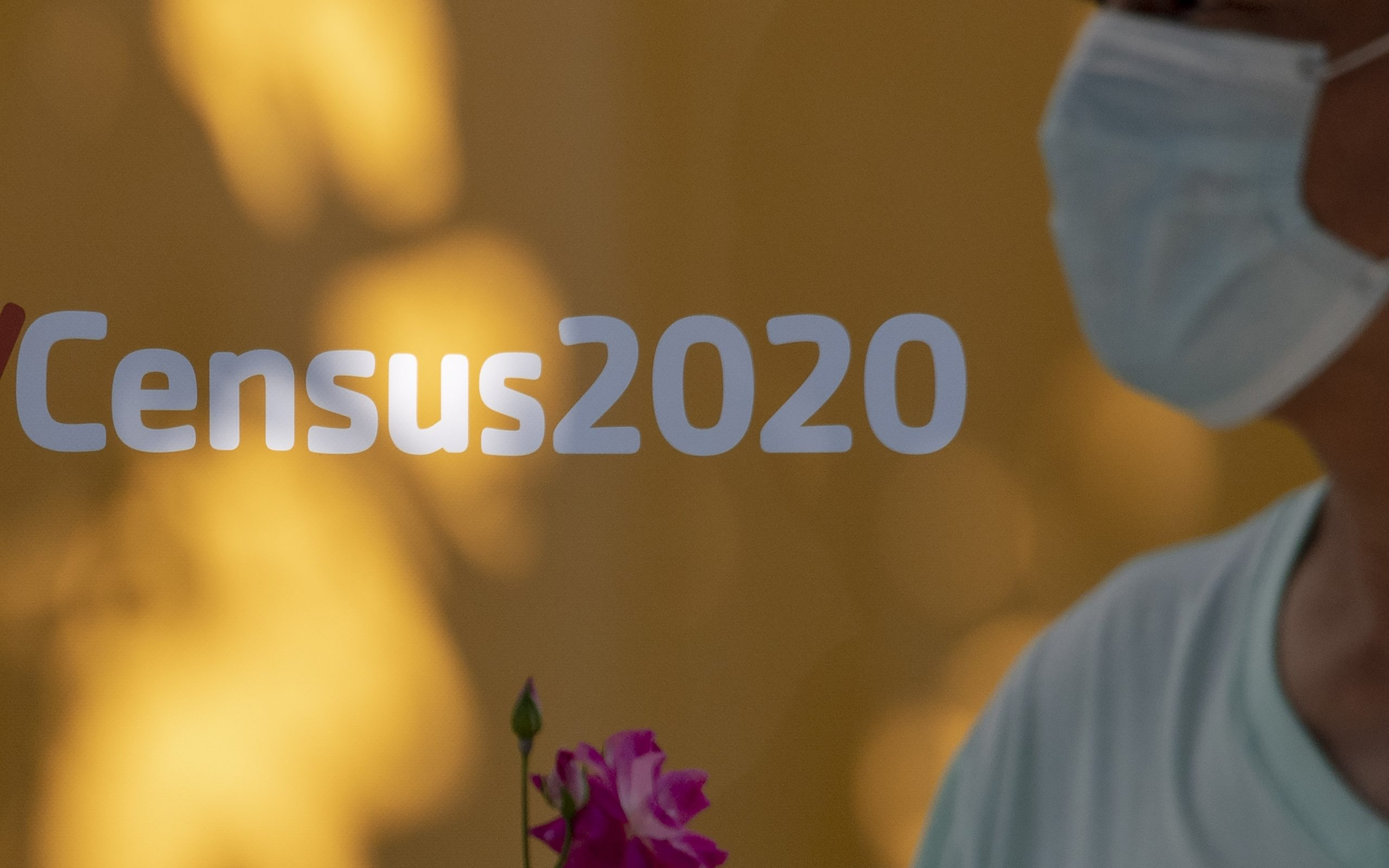 A man wearing a facemask walks past a sign encouraging people to complete the 2020 US Census, in Los Angeles, California, August 10, 2020 amid the COVID-19 pandemic. - The result of the Census, which the Census Bureau announced it would end one month early, on September 30, directly affects the amount of funding a community receives for services including public schools, hospitals and fire departments. (Photo by ROBYN BECK/AFP via Getty Images)