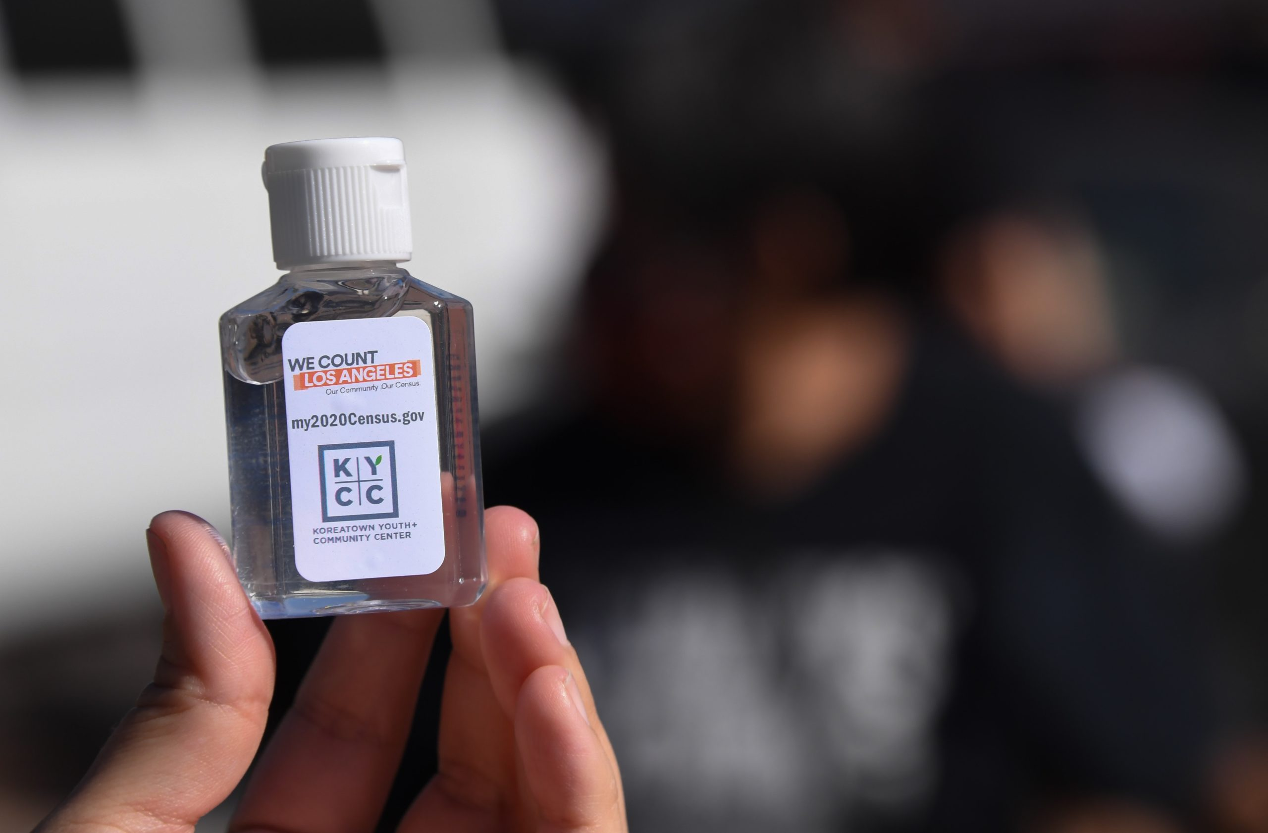 A volunteer displays a bottle of hand sanitzer labeled with information about the US Census which she is passing out to encourage people to complete the Census, at a food distribution bank for people facing economic hardship or food insecurity, in a church parking lot in Los Angeles, California, August 10, 2020 amid the COVID-19 pandemic. - The result of the Census, which the Census Bureau announced it would end one month early, on September 30, directly affects the amount of funding a community receives for services including public schools, hospitals and fire departments. (Photo by Robyn Beck / AFP) (Photo by ROBYN BECK/AFP via Getty Images)