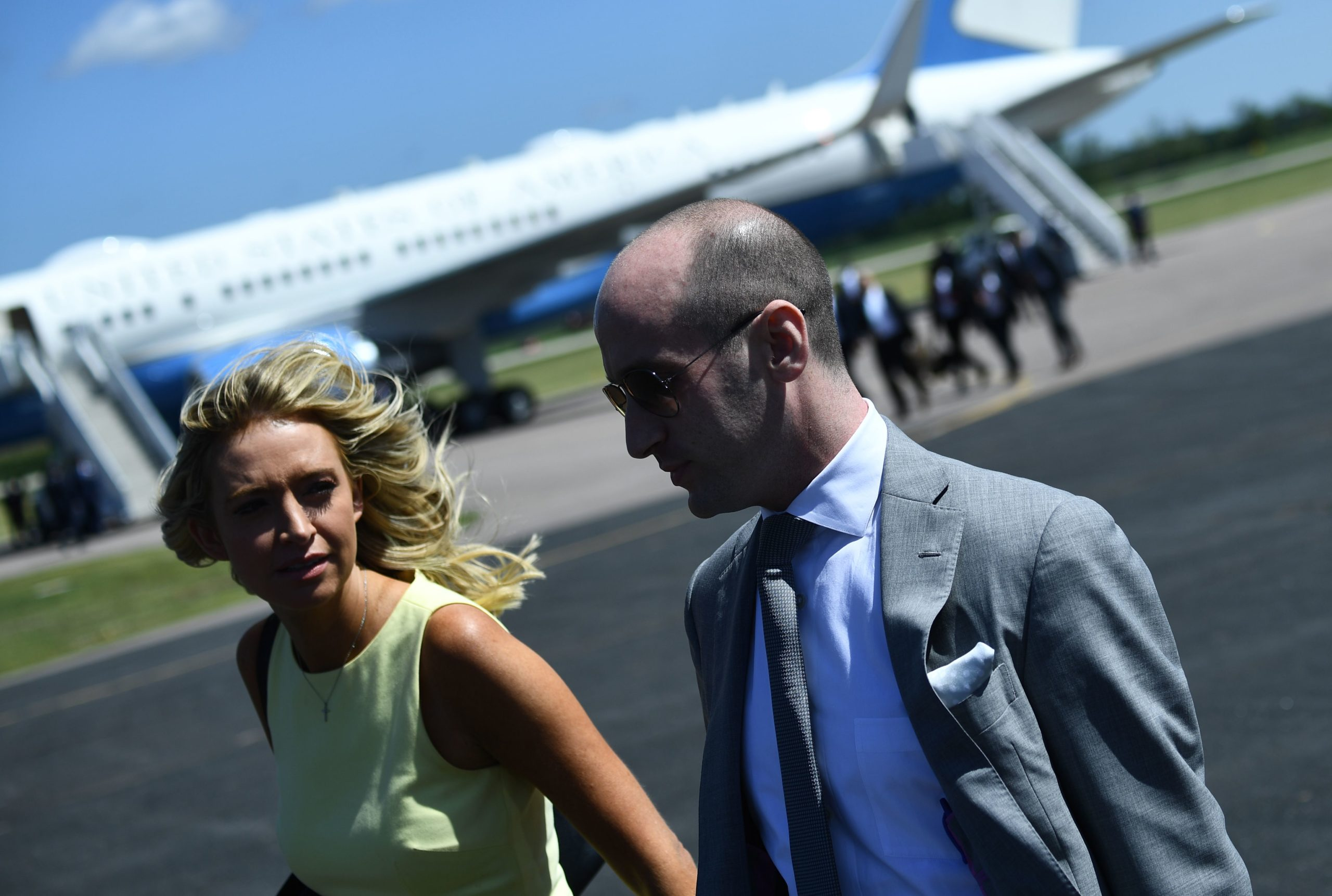 White House Press Secretary Kayleigh McEnany (L) and presidential advisor Stephen Miller walk on the tarmac before US President Donald Trump steps off Airforce One on August 17, 2020 in Mankato, Minnesota, to deliver remarks on the economy. (Photo by BRENDAN SMIALOWSKI/AFP via Getty Images)