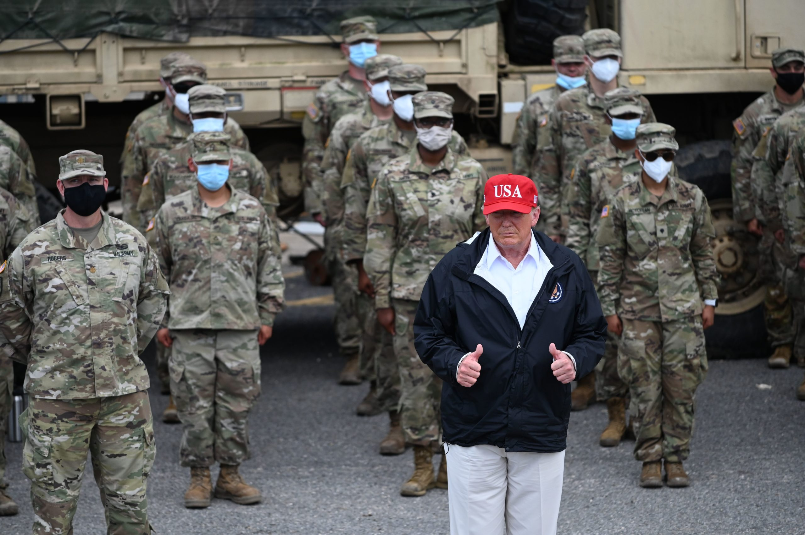 US President Donald Trump poses with National Guard troops in Lake Charles, Louisiana, on August 29, 2020. Trump surveyed damage in the area caused by Hurricane Laura. - At least 15 people were killed after Laura slammed into the southern US states of Louisiana and Texas, authorities and local media said on August 28. (Photo by Roberto Schmidt/AFP via Getty Images)
