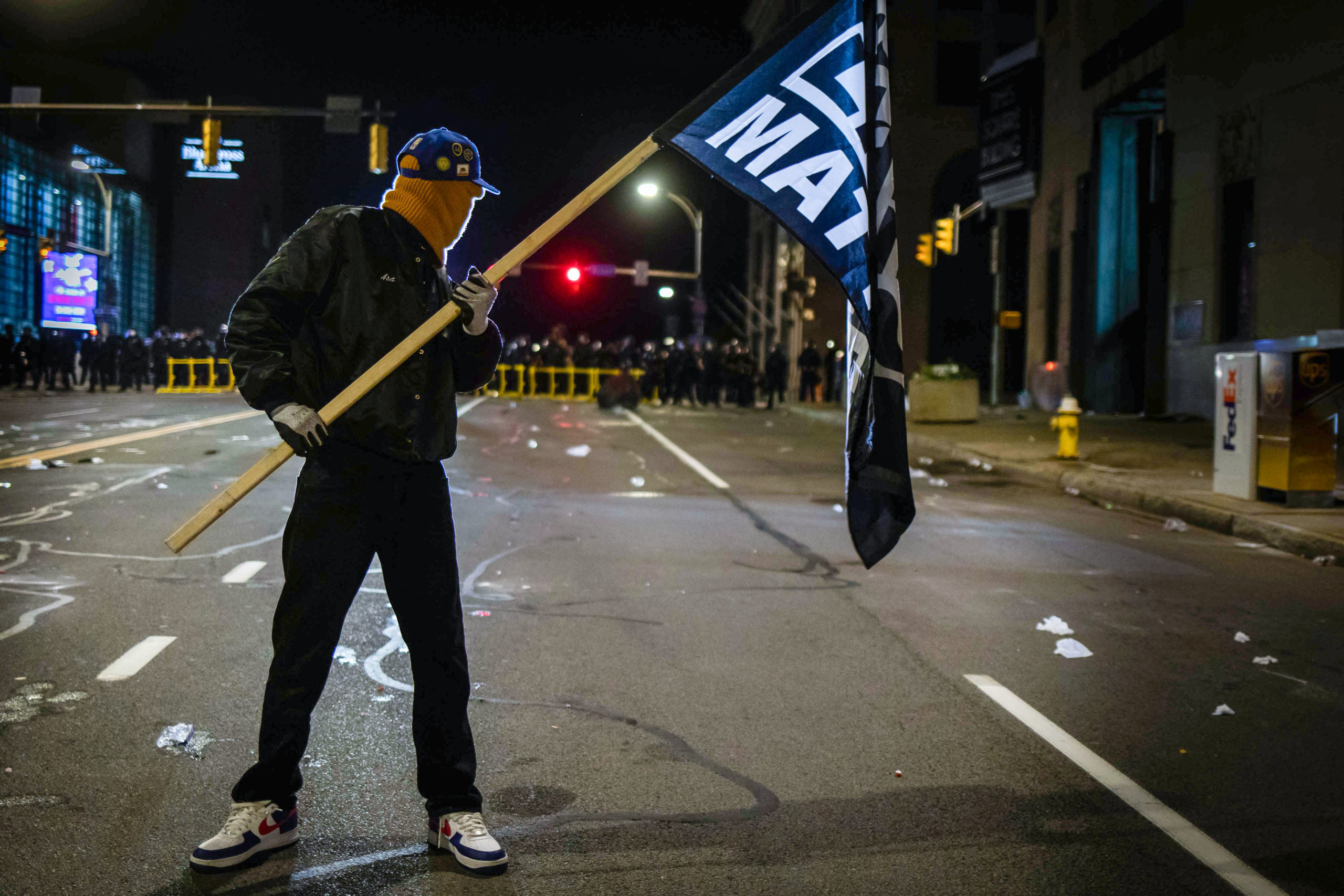 "A protester wearing a Black Panther jacket and holding a ""Black Lives Matter"" flag faces off with riot police in Rochester, New York, on September 5, 2020, on the fourth night of protest following the release of video showing the death of Daniel Prude. - Prude, a 41-year-old African American who had mental health issues, died of asphyxiation after police arrested him on March 23, 2020, in Rochester. (MARANIE R. STAAB/AFP via Getty Images)"