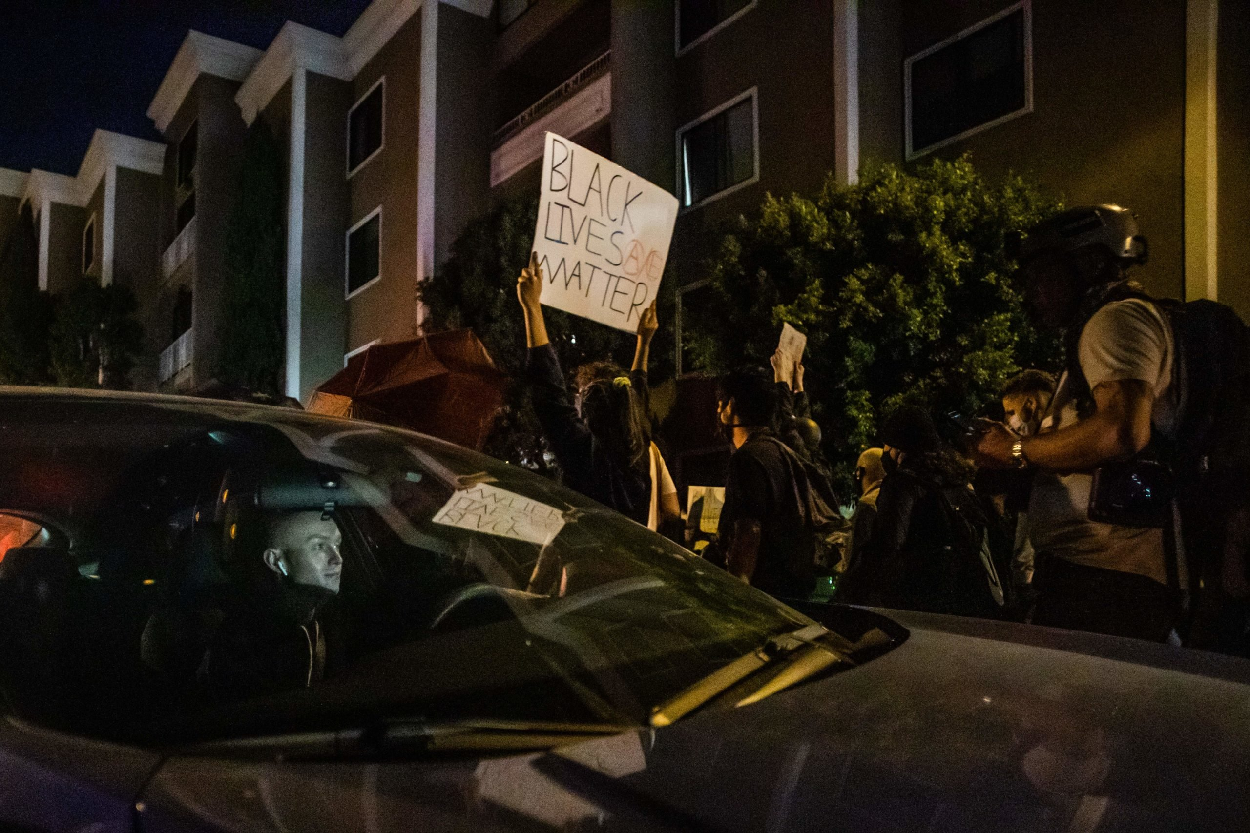 A driver stuck in the protest watches demonstrators passing by his car as they manifest their discontent over the lack of criminal charges in the police killing of Breonna Taylor in West Hollywood, California on September 25, 2020. - The family of Breonna Taylor today, September 25, demanded that US authorities release grand jury transcripts showing why no police will face direct criminal charges over her death, which has once again galvanized protesters angry about racism and police brutality in America. (Photo by Apu GOMES / AFP) (Photo by APU GOMES/AFP via Getty Images)