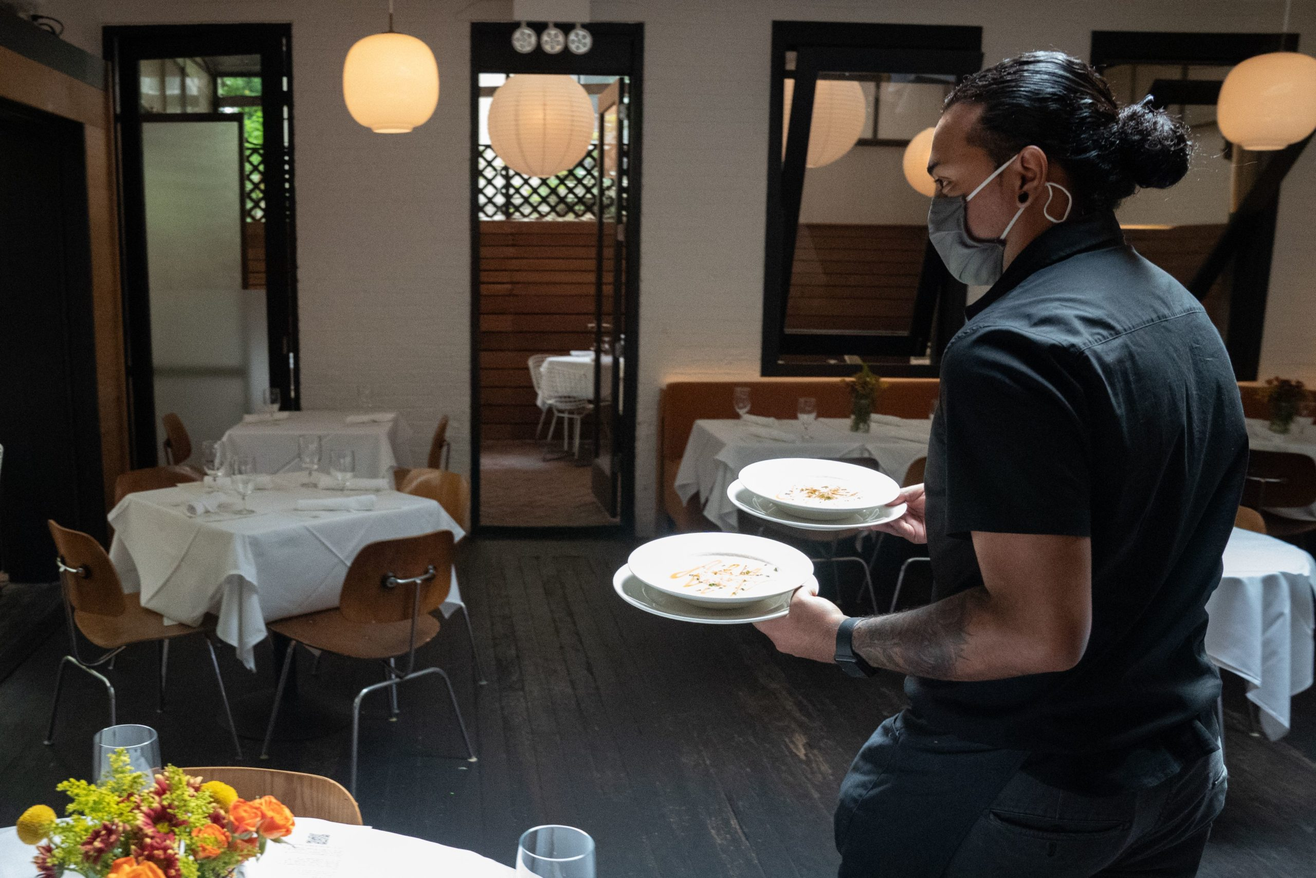 A waiter delivers food to a table at Bottino Restaurant in Chelsea as New York City restaurants open for limited capacity indoor dining on October 1, 2020 in New York. (Photo by Bryan R. Smith / AFP) (Photo by BRYAN R. SMITH/AFP via Getty Images)
