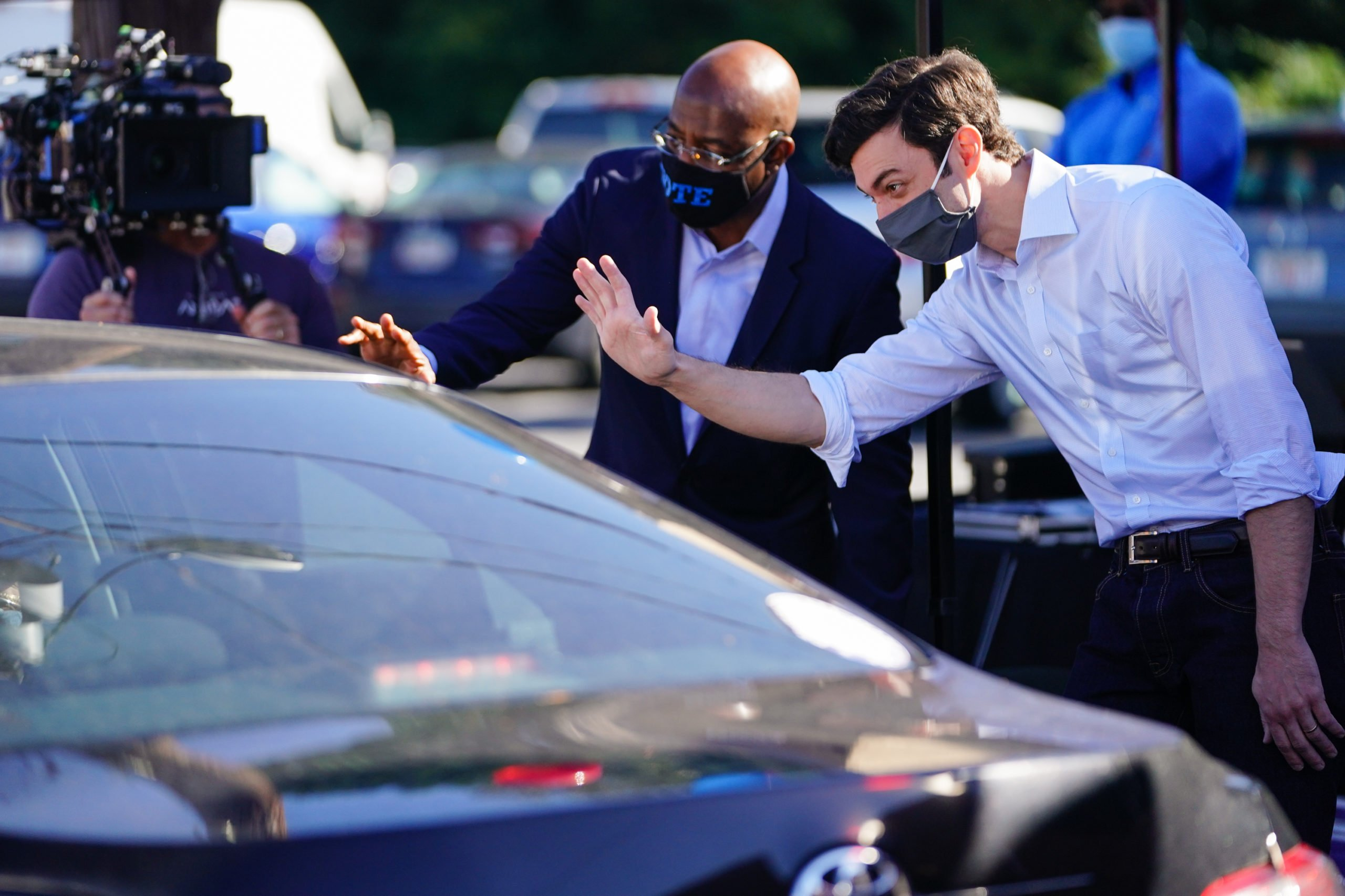 Democratic U.S. Senate candidates Jon Ossoff and Rev. Raphael Warnock hand out lawn signs at a campaign event on October 3, 2020 in Lithonia, Georgia. The two are hoping to unseat incumbent Senators David Perdue and Kelly Loeffler. (Elijah Nouvelage/Getty Images)