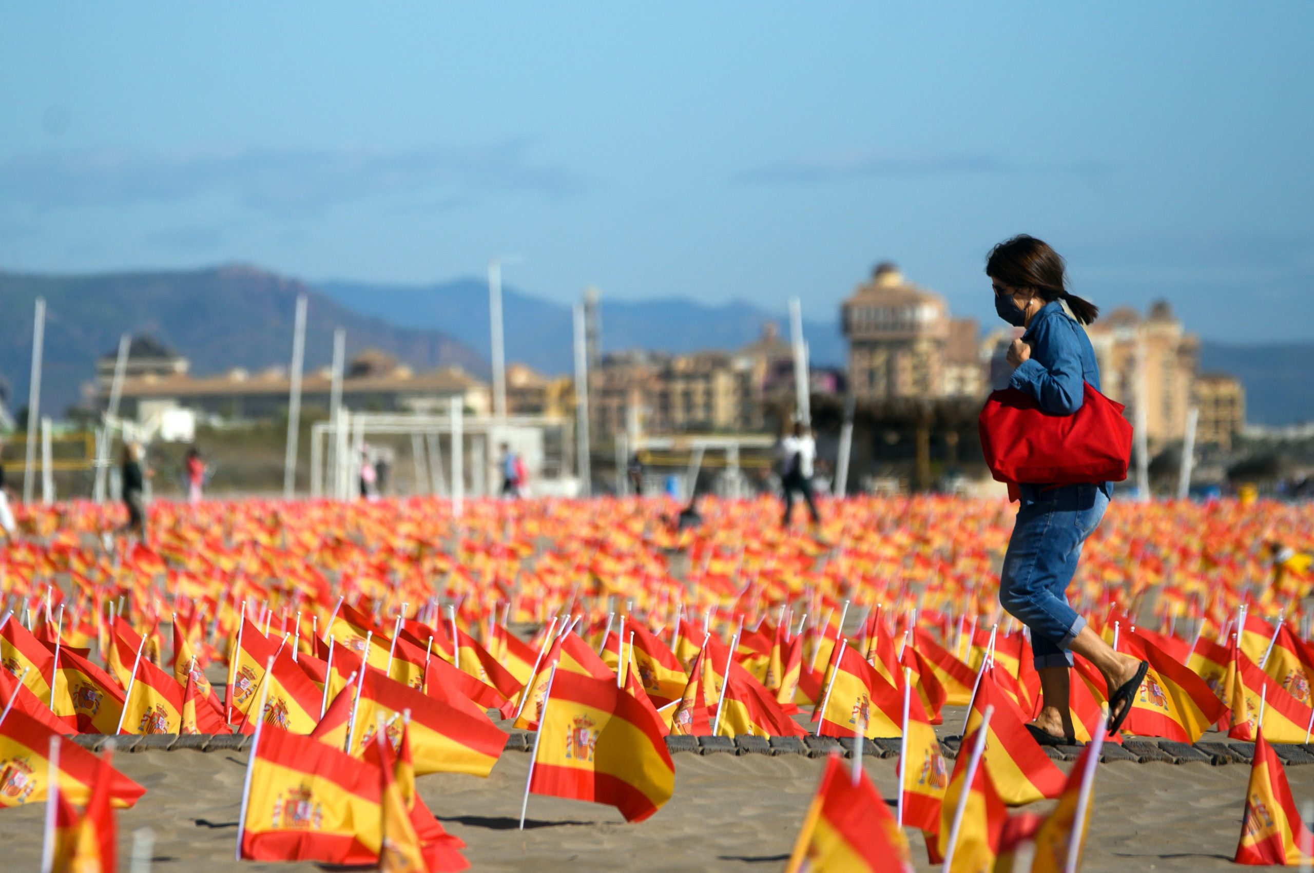 A woman walks among thousands of Spanish flags, representing the Spanish victims of coronavirus, on Patacona beach in Valencia, on Oct. 4. (Jose Jordan/AFP via Getty Images)