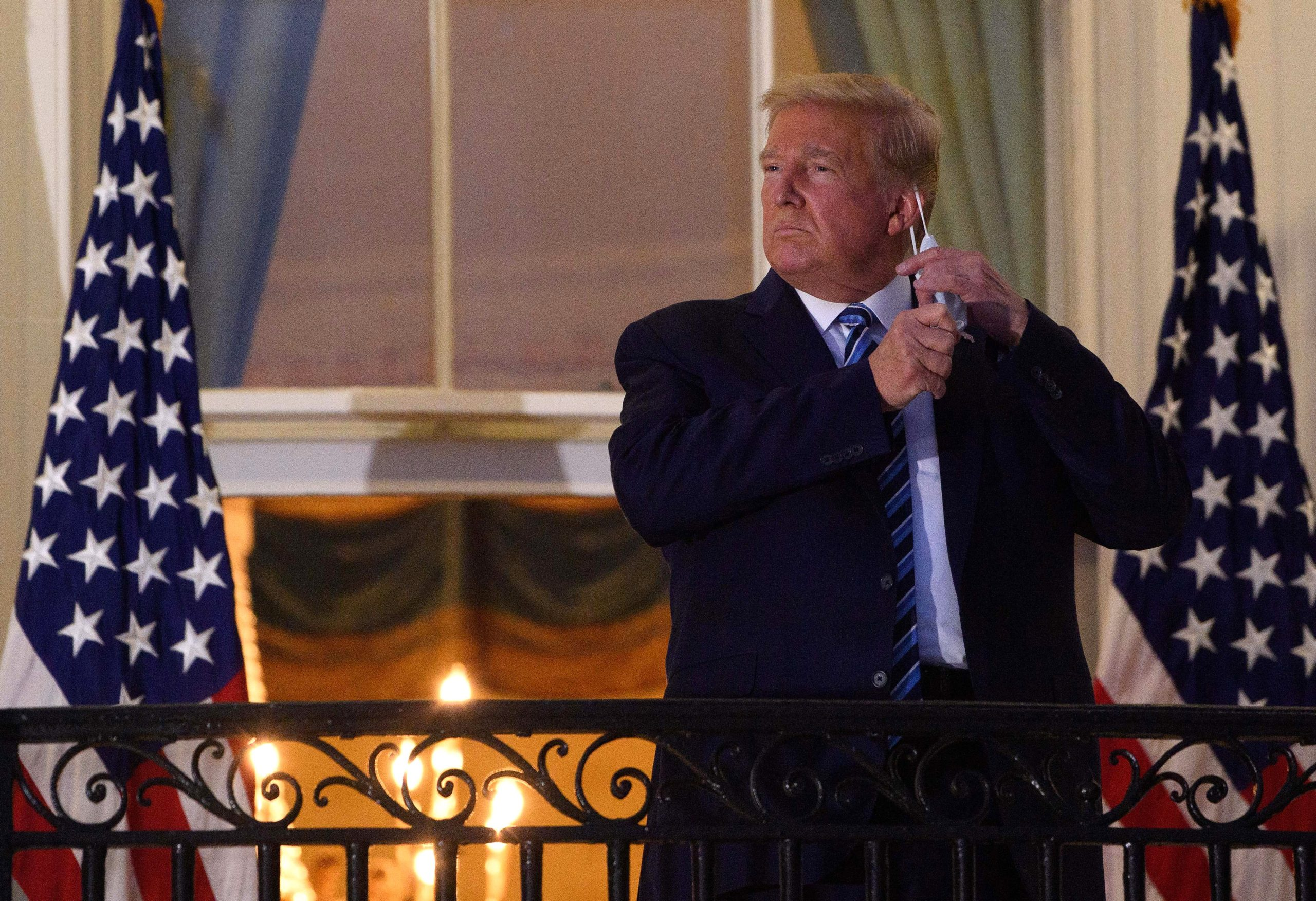 President Donald Trump takes off his mask as he arrives at the White House upon his return from Walter Reed Medical Center on Oct. 5. (Nicholas Kamm/AFP via Getty Images)