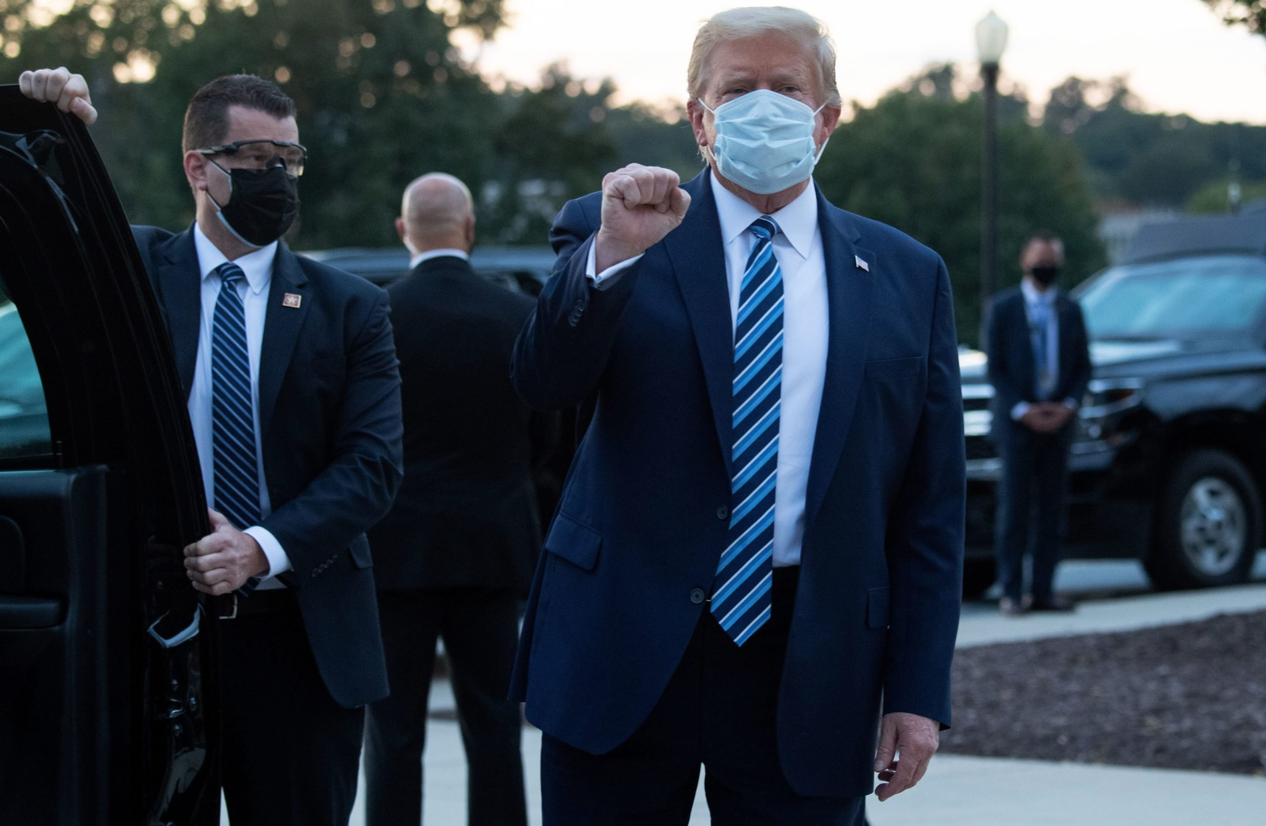 """US President Donald Trump pumps his fist as he leaves Walter Reed Medical Center in Bethesda, Maryland heading towards Marine One on October 5, 2020, to return to the White House after being discharged. - Trump announced Monday he would be """"back on the campaign trail soon"""", just before returning to the White House from a hospital where he was being treated for Covid-19. (Photo by SAUL LOEB/AFP via Getty Images)"""