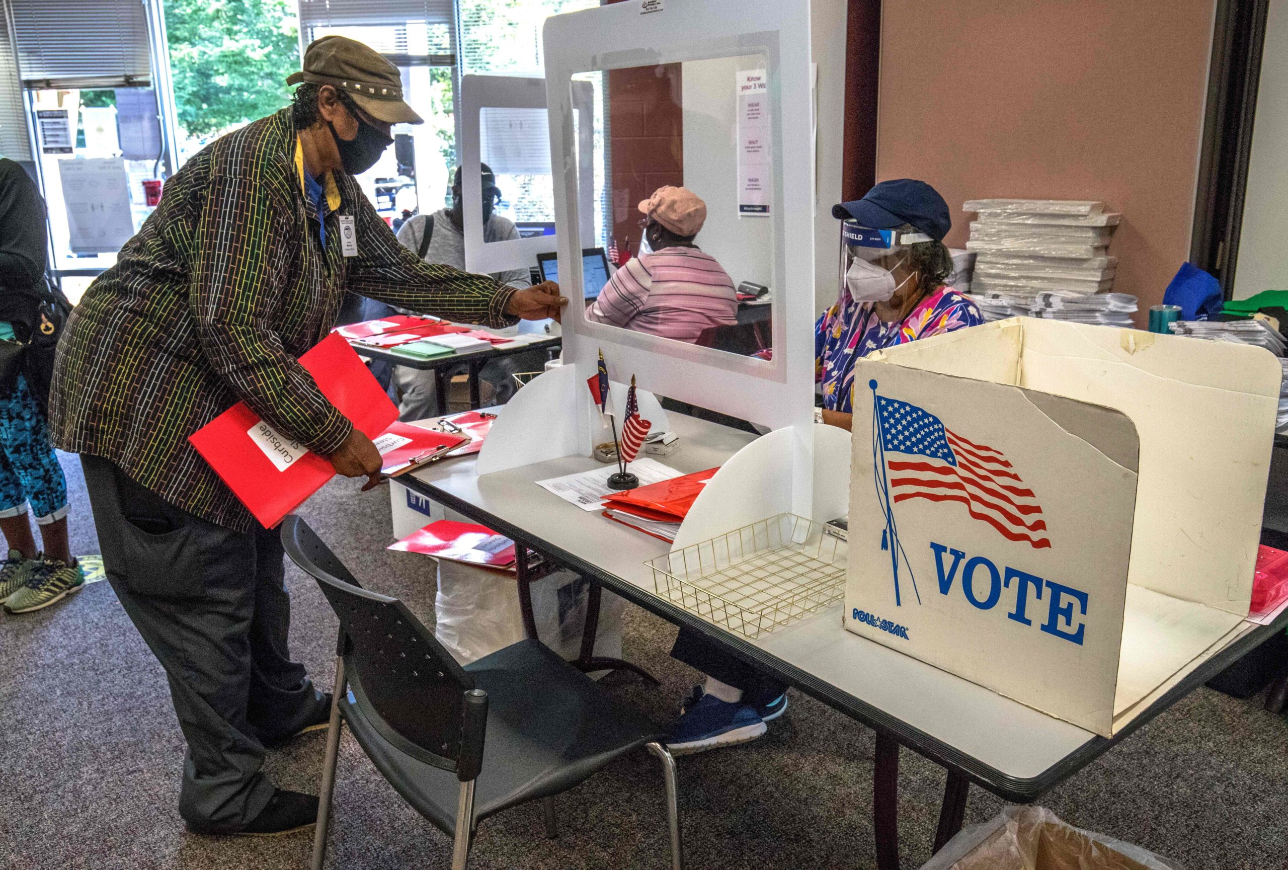 A poll worker (R) assists voters as they enter the West Boulevard branch of the Mecklenburg County library in Charlotte, North Carolina, on October 15, 2020, during the first day of early voting. (Photo by Grant Baldwin / AFP) (Photo by GRANT BALDWIN/AFP via Getty Images)
