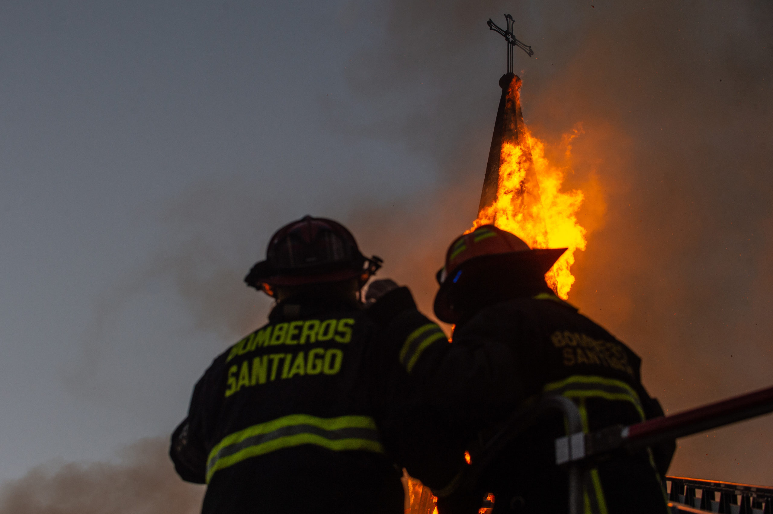Firemen attempt to put out a church which has caught fire during a protest on October 18, 2020 in Santiago, Chile. A series of protests and social unrest arose on October 18, 2019, after a subway fare increase. It developed in a movement demanding improvements in basic services, fair prices and benefits including pensions, public health, and education. As a result, Chile will hold a referendum next Sunday to to decide whether or not to modify the Pinochet-era constitution. (Claudio Santana/Getty Images)