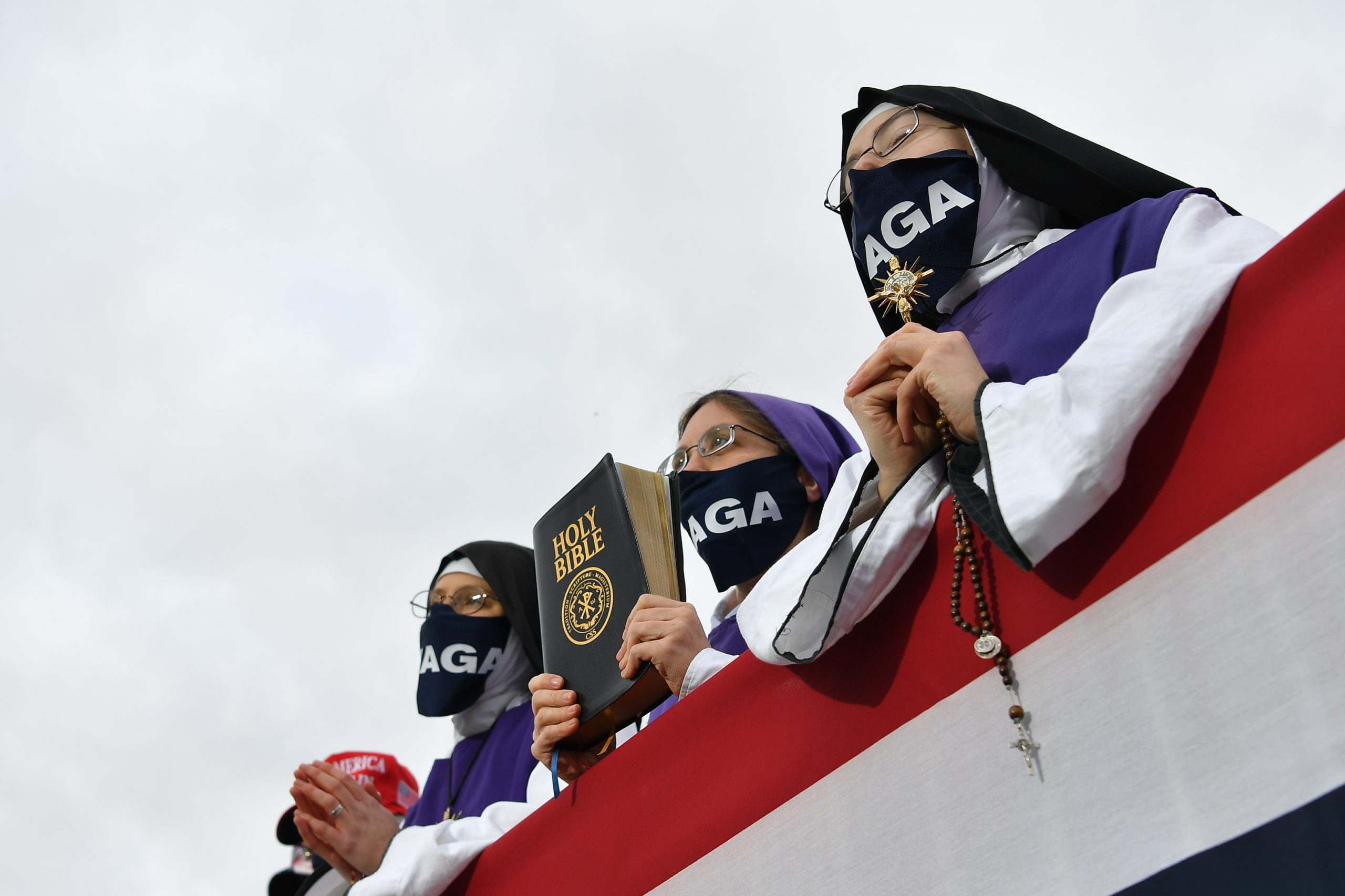 Nuns wearing masks displaying Trump's MAGA slogan listen as US President Donald Trump speaks during a campaign rally at Pickaway Agriculture and Event Center in Circleville, Ohio on October 24, 2020.  (MANDEL NGAN/AFP via Getty Images)