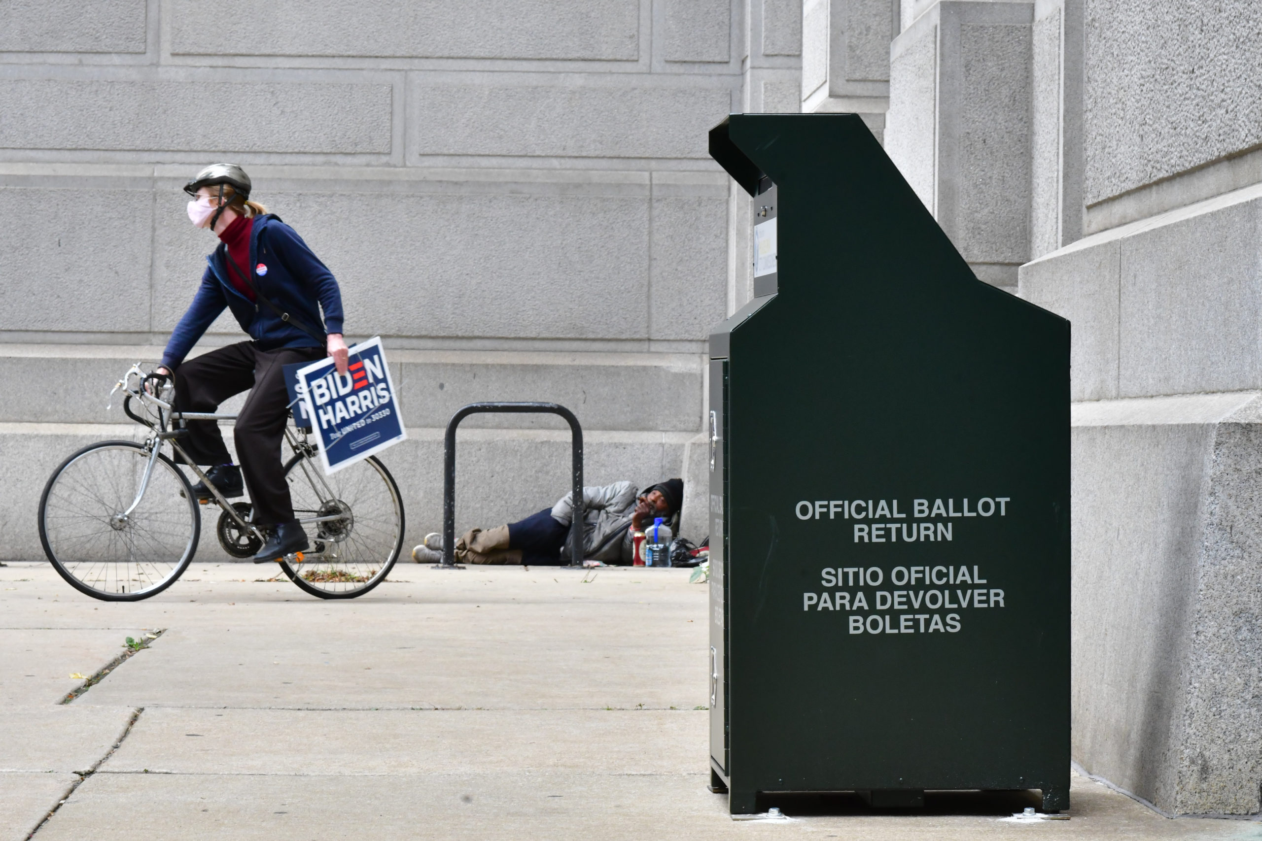 A woman holding a Biden-Harris campaign placard cycles away after casting her ballot at the Philadelphia City Hall satellite polling station on Oct. 27. (Mark Makela/Getty Images)