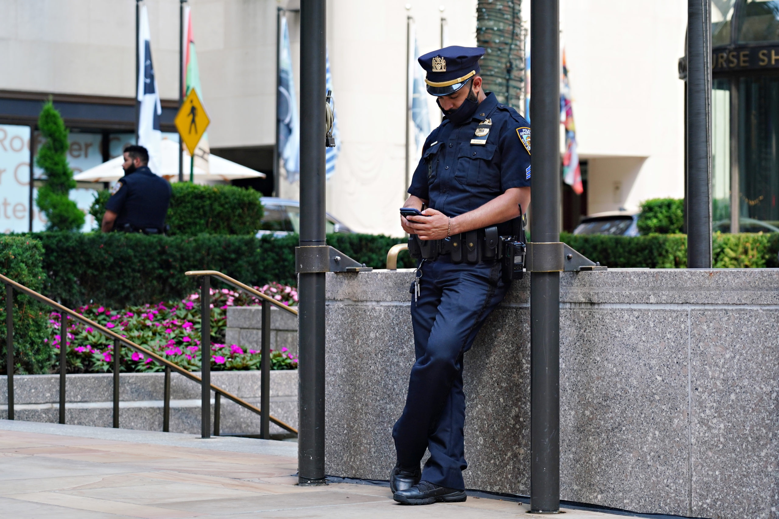 NEW YORK, NEW YORK - AUGUST 01: An NYPD officer wearing a protective mask looks at his phone at Rockefeller Center as the city continues Phase 4 of re-opening following restrictions imposed to slow the spread of coronavirus on August 1, 2020 in New York City. The fourth phase allows outdoor arts and entertainment, sporting events without fans and media production. (Cindy Ord/Getty Images)